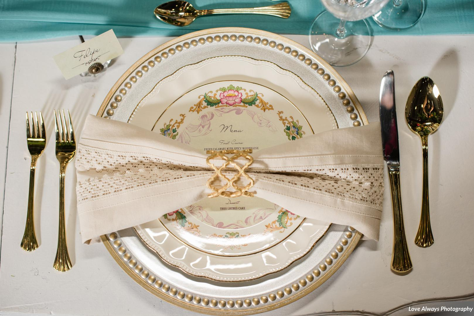 elegant wedding place setting with ivory napkin, gold napkin wring, ivory plates, gold and silver charge, and gold tableware