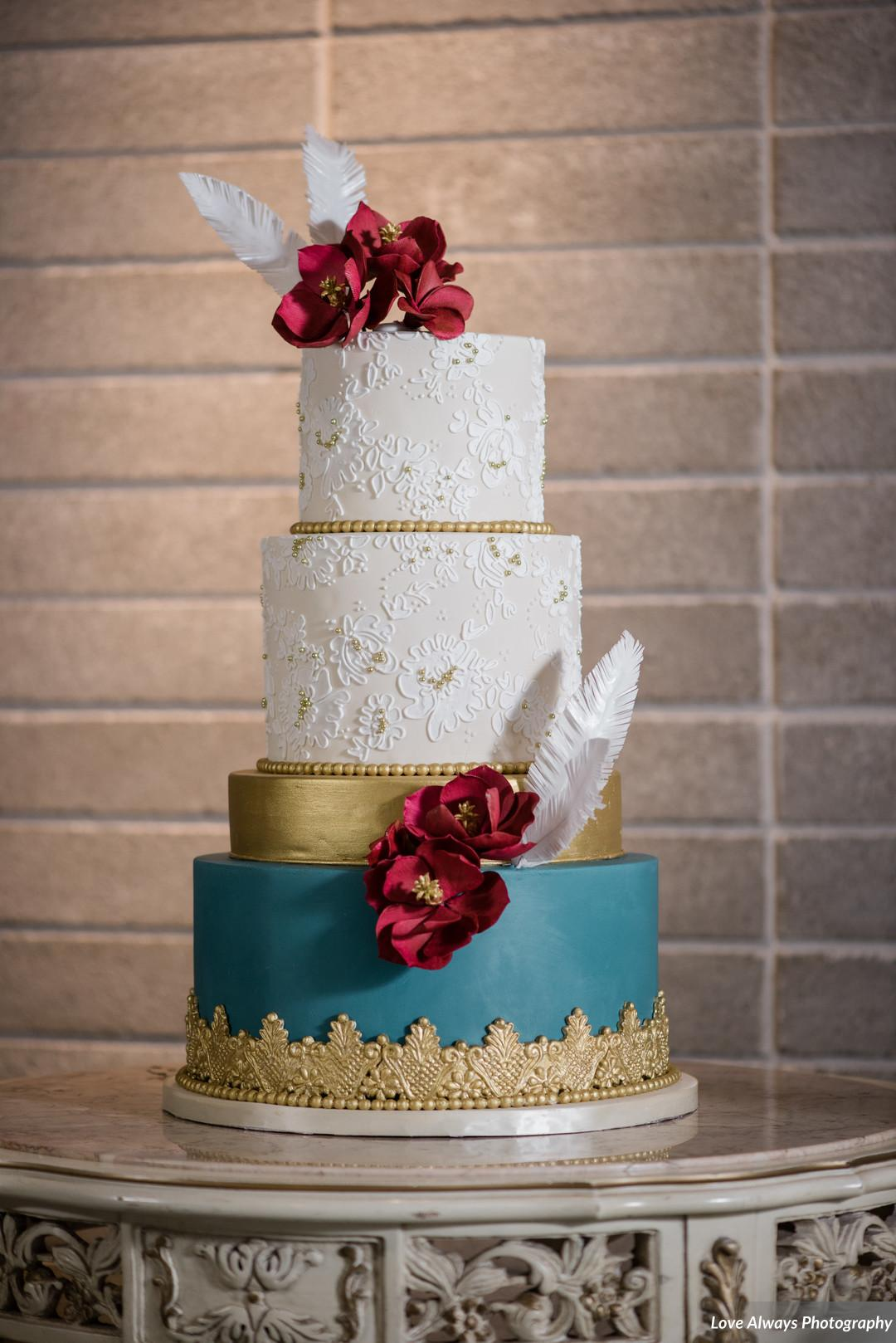 elegant teal, gold and ivory wedding cake with burgundy flower and white feather detail - by la rose bakery milton