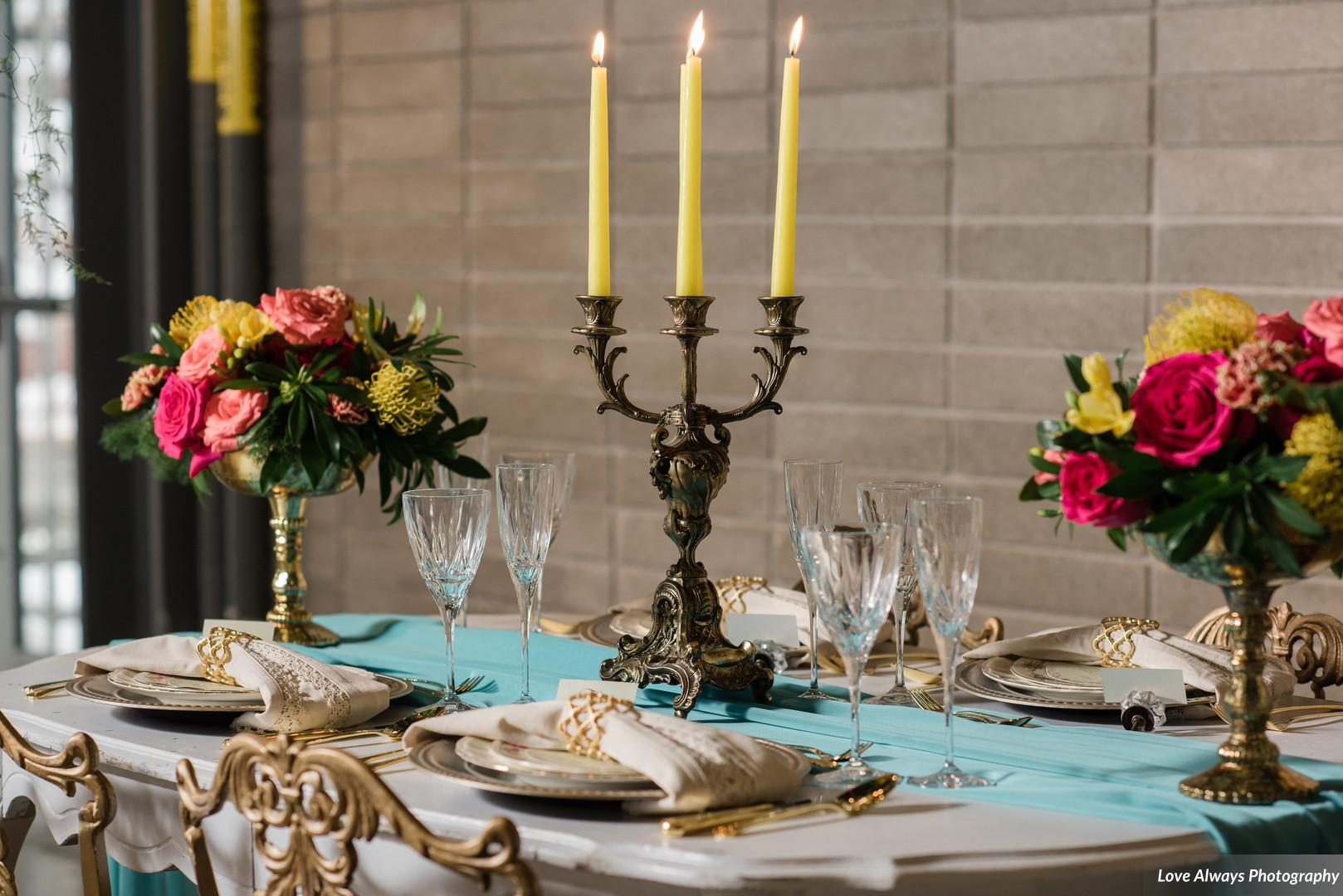 Intimate tropical dinner party with bright flowers and yellow candles
