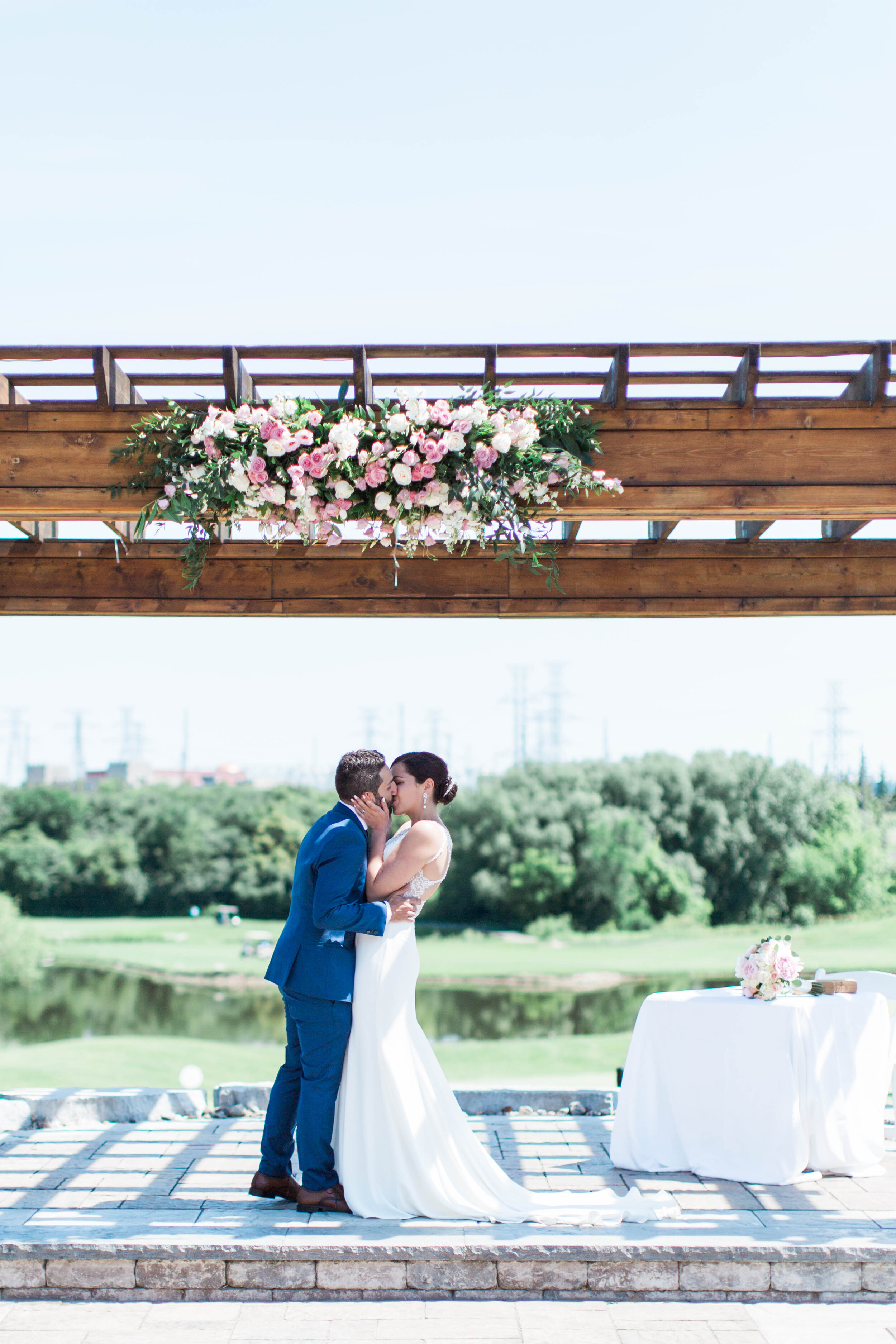 Bride and Groom Kiss Under Wedding Arbour - Trendy Modern Brunch Wedding - Historia Wedding and Event Planning