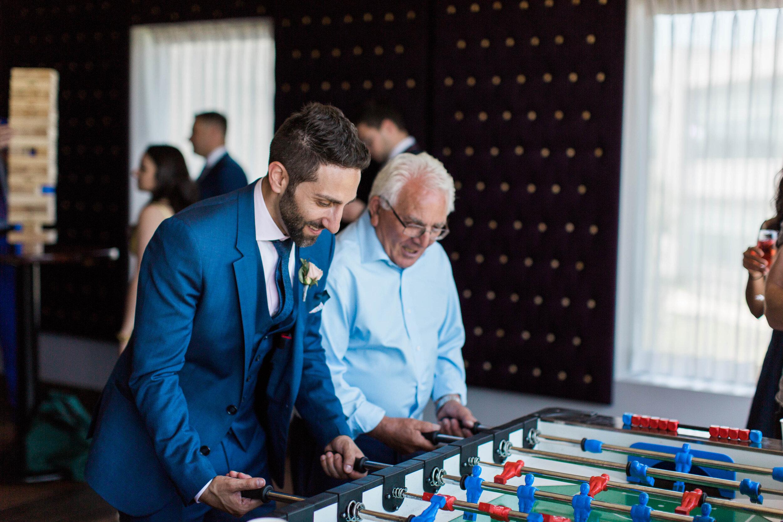 Groom Playing Foosball - Trendy Modern Brunch Wedding - Historia Wedding and Event Planning