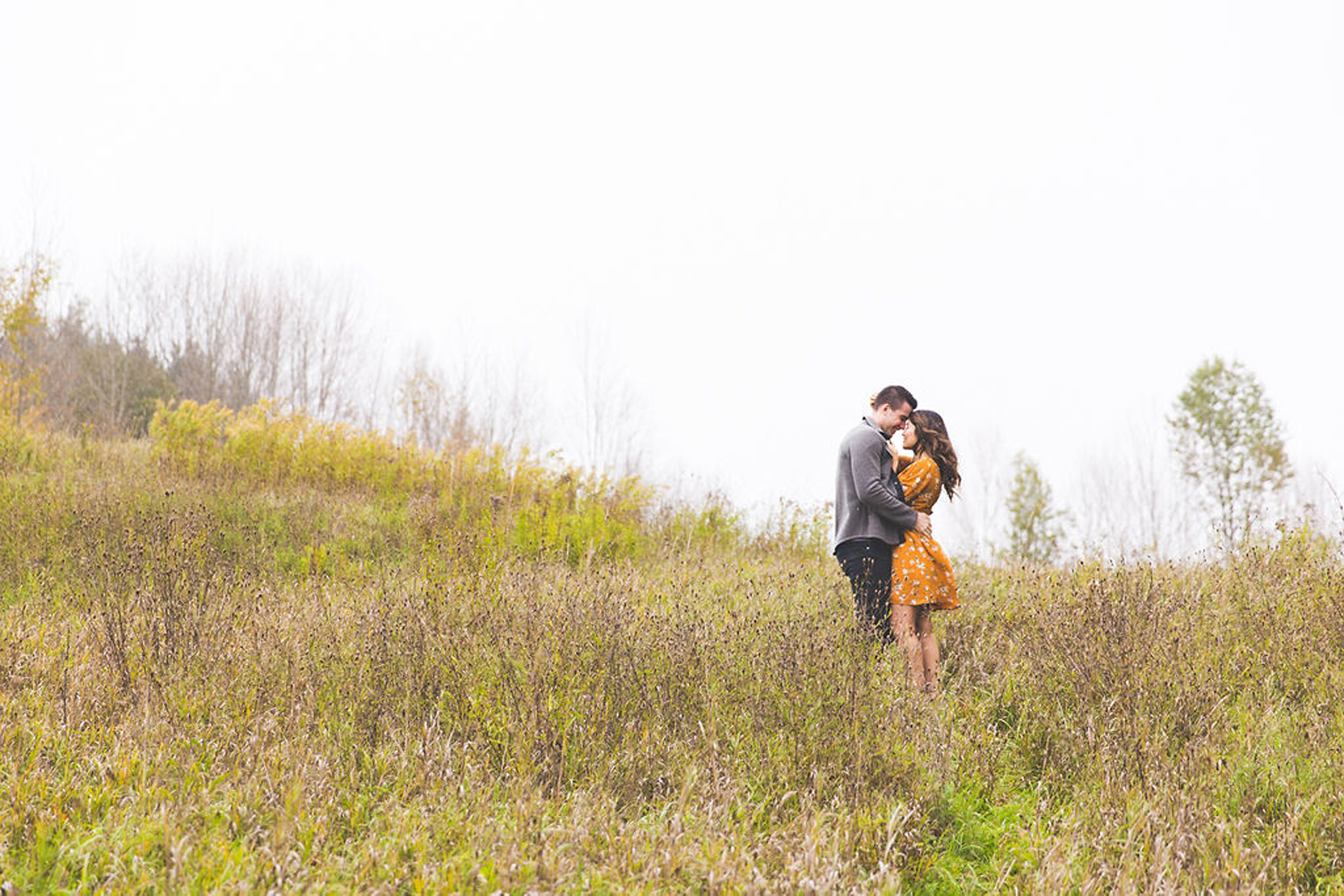 Cozy couple in an Owen Sound field during an engagement session