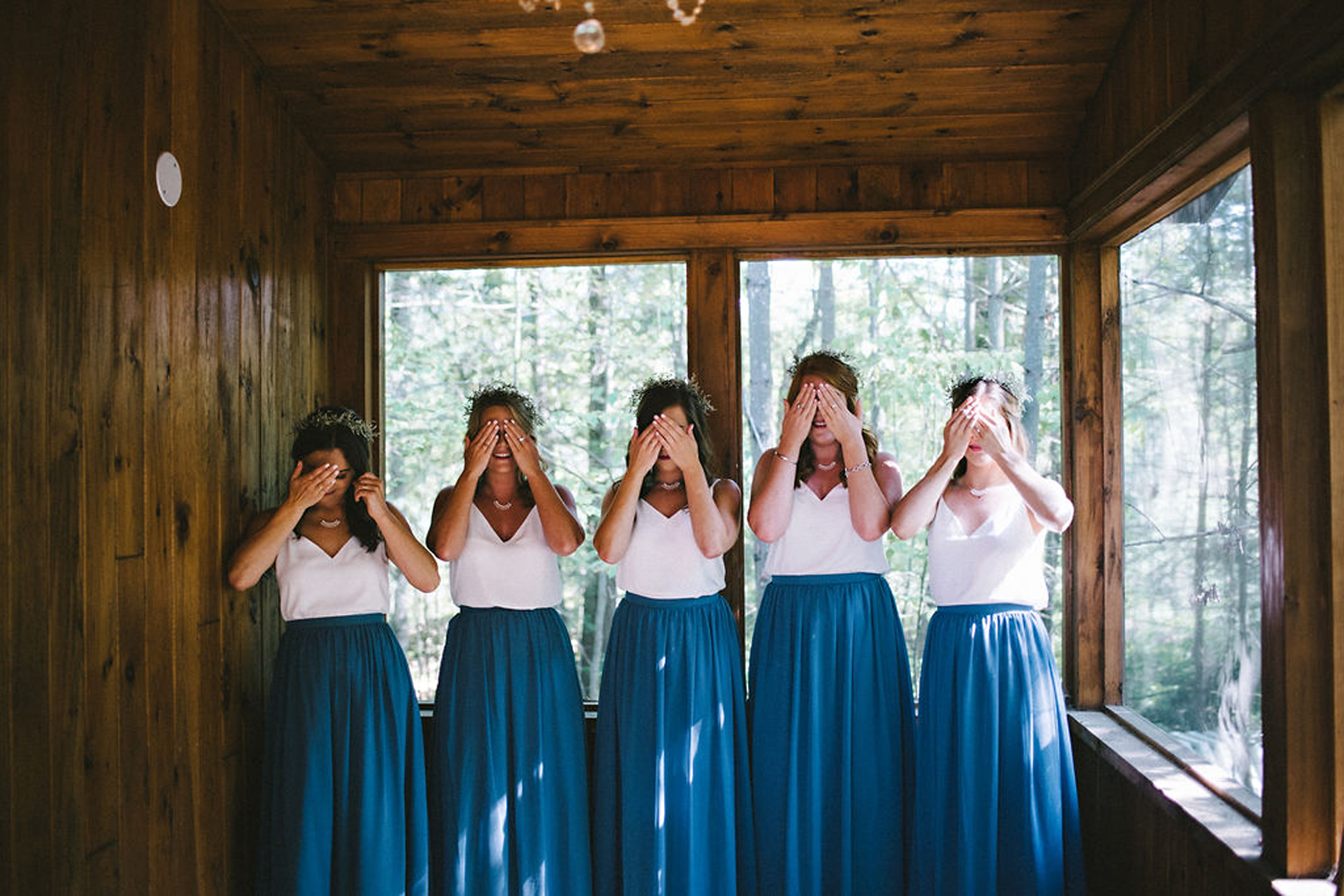 Bridesmaids wearing blue skirts and white camisoles