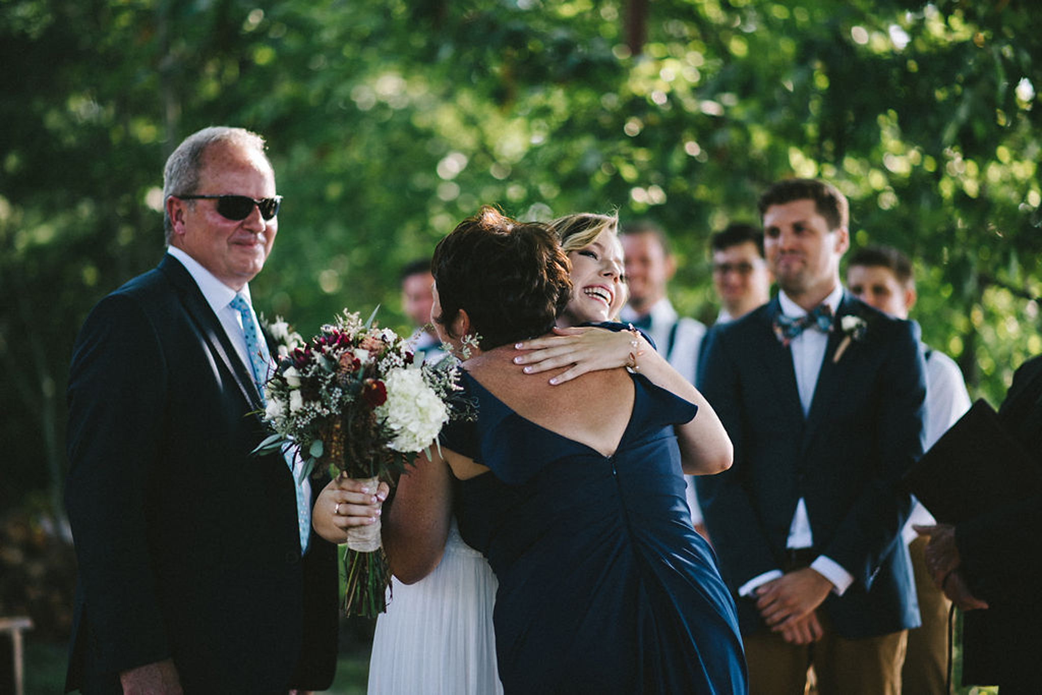 Bride hugging mother at lakeside Parry Sound camp wedding