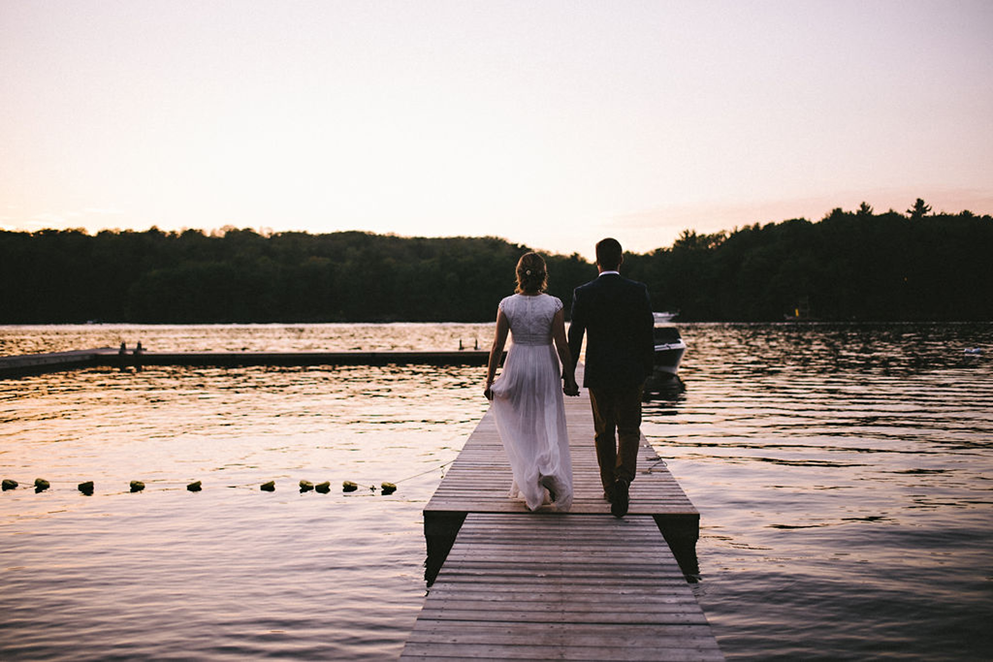 Bride and Groom walking on dock at Parry Sound camp wedding