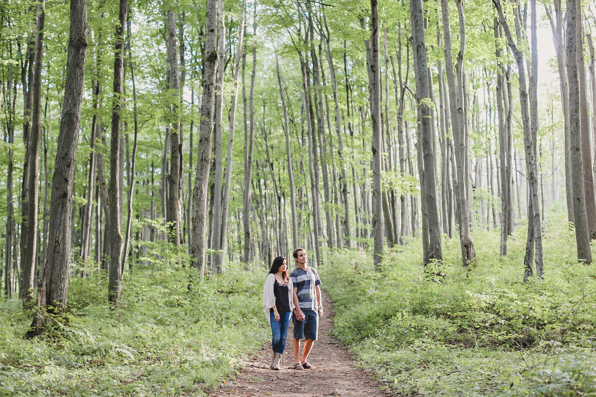 Engaged couple walking through the mixed forest at Castle Glen