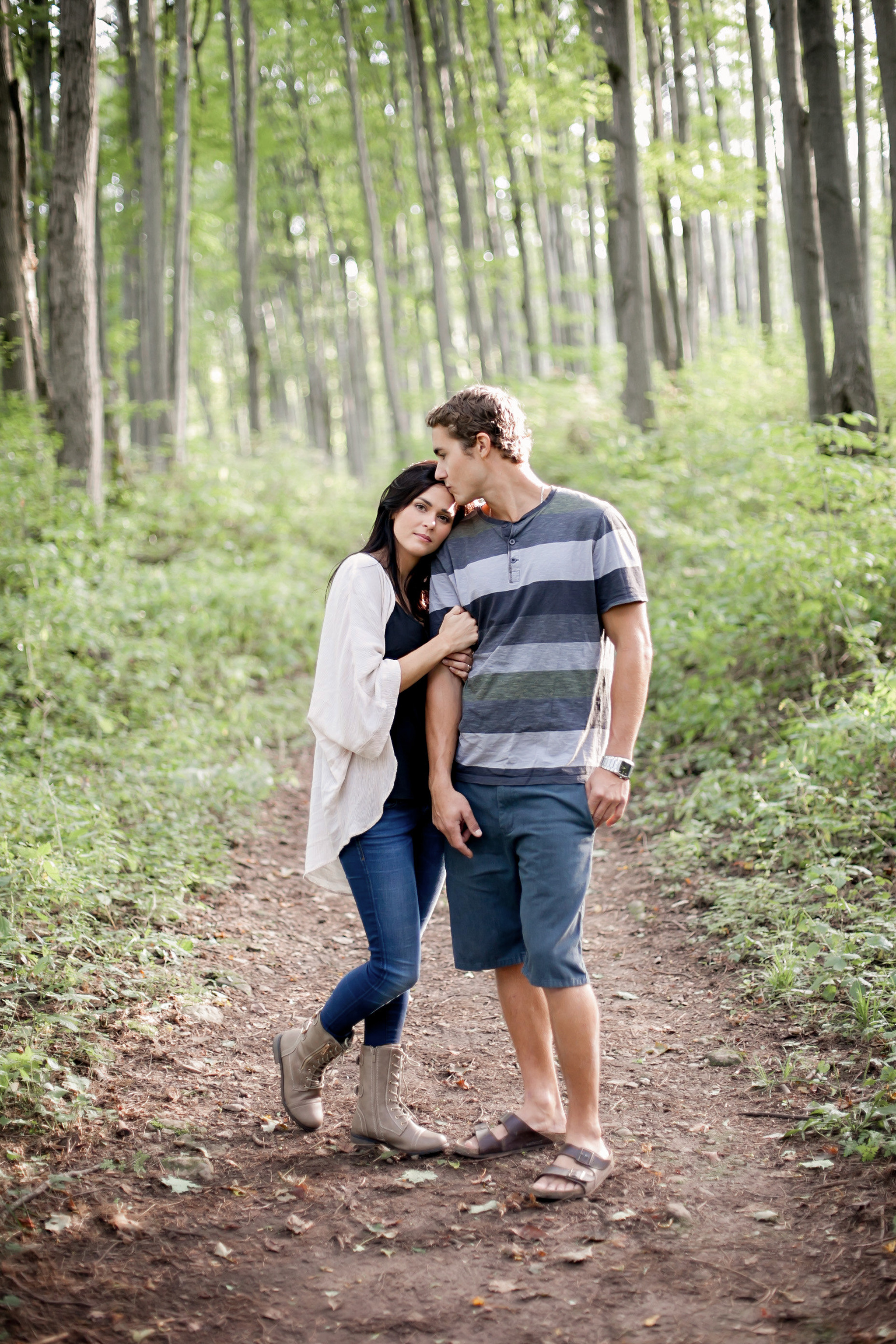 Newly engaged couple stroll through forest at Castle Glen Estate