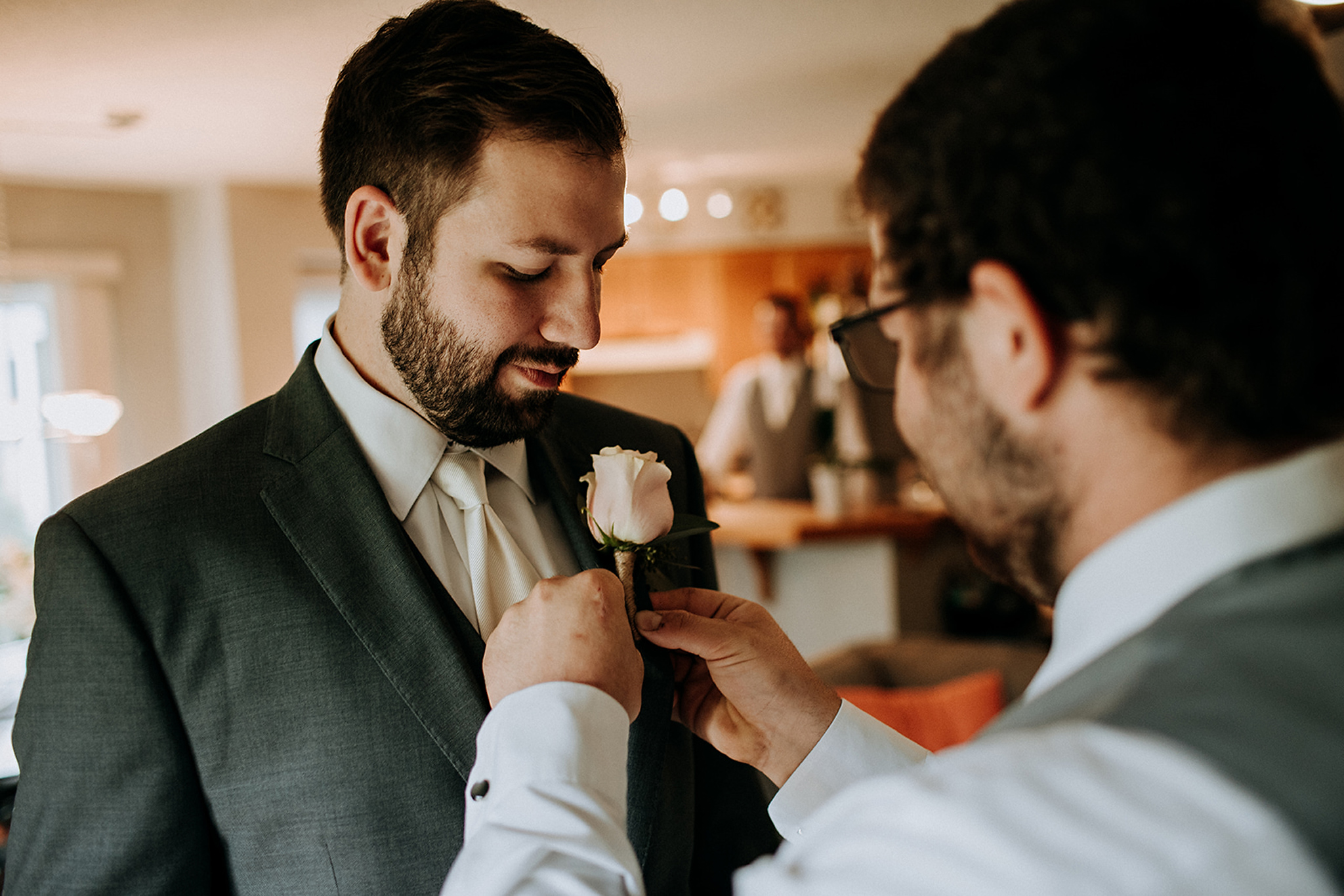 pinning a boutonniere on the groom at meaford barn wedding