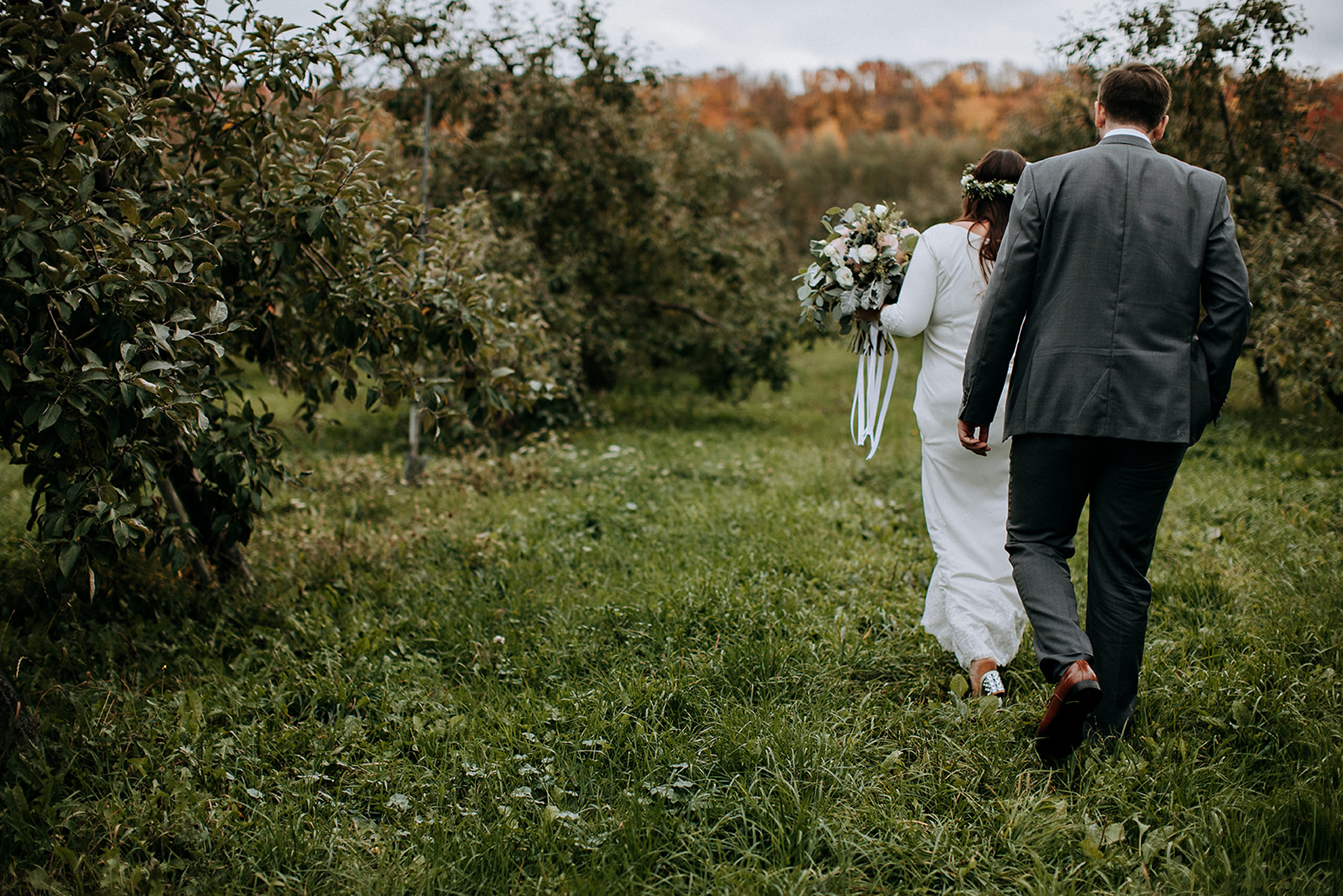 couple heading into apple orchard at meaford barn wedding