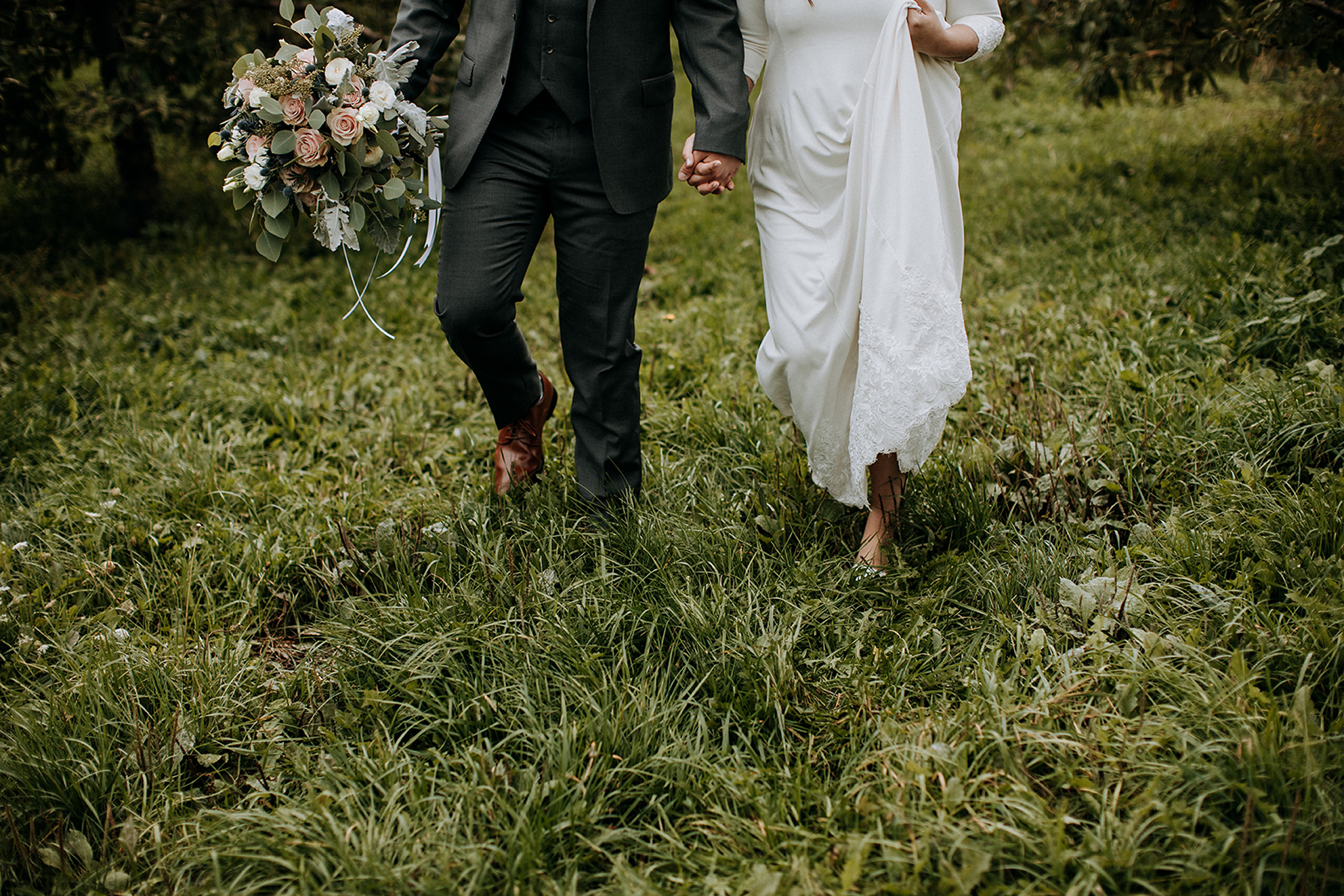 couple walking through apple orchard at meaford barn wedding