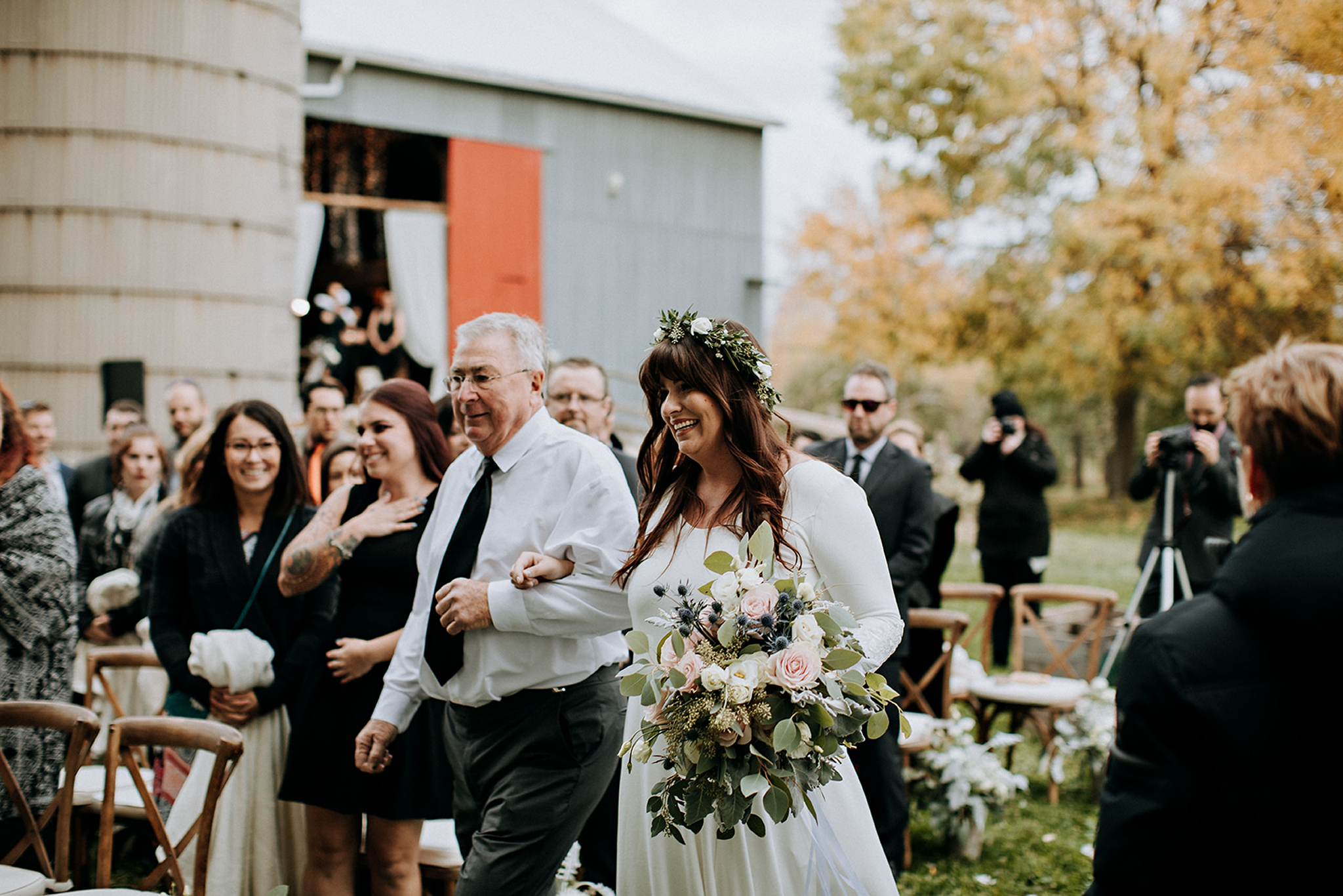 bride walks down the aisle with her dad at meaford barn wedding