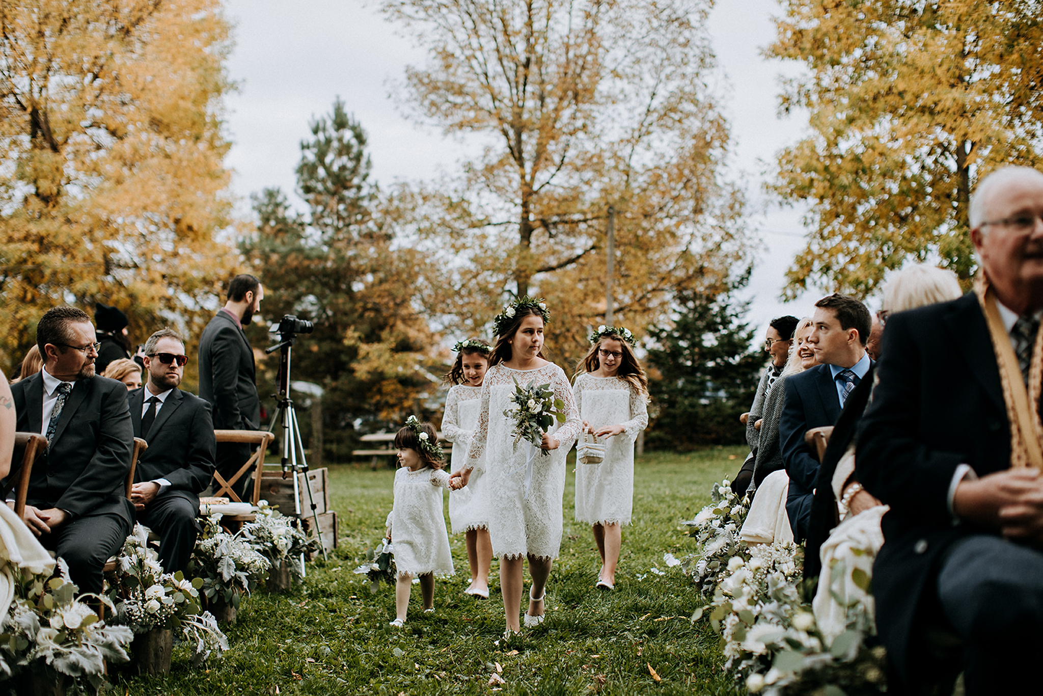 flowers girl walk down the grass walkway at meaford barn wedding