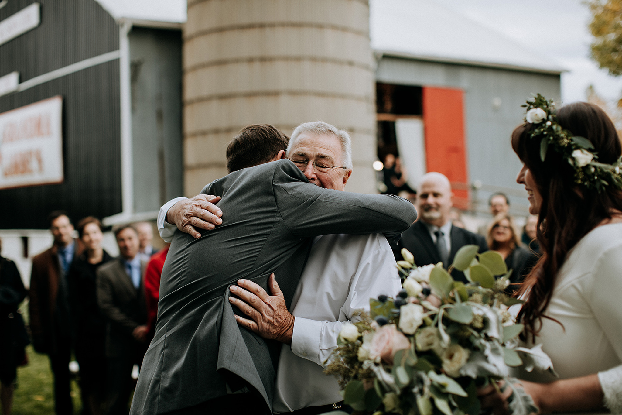 father of the bride welcomes groom into family at outdoor ceremo