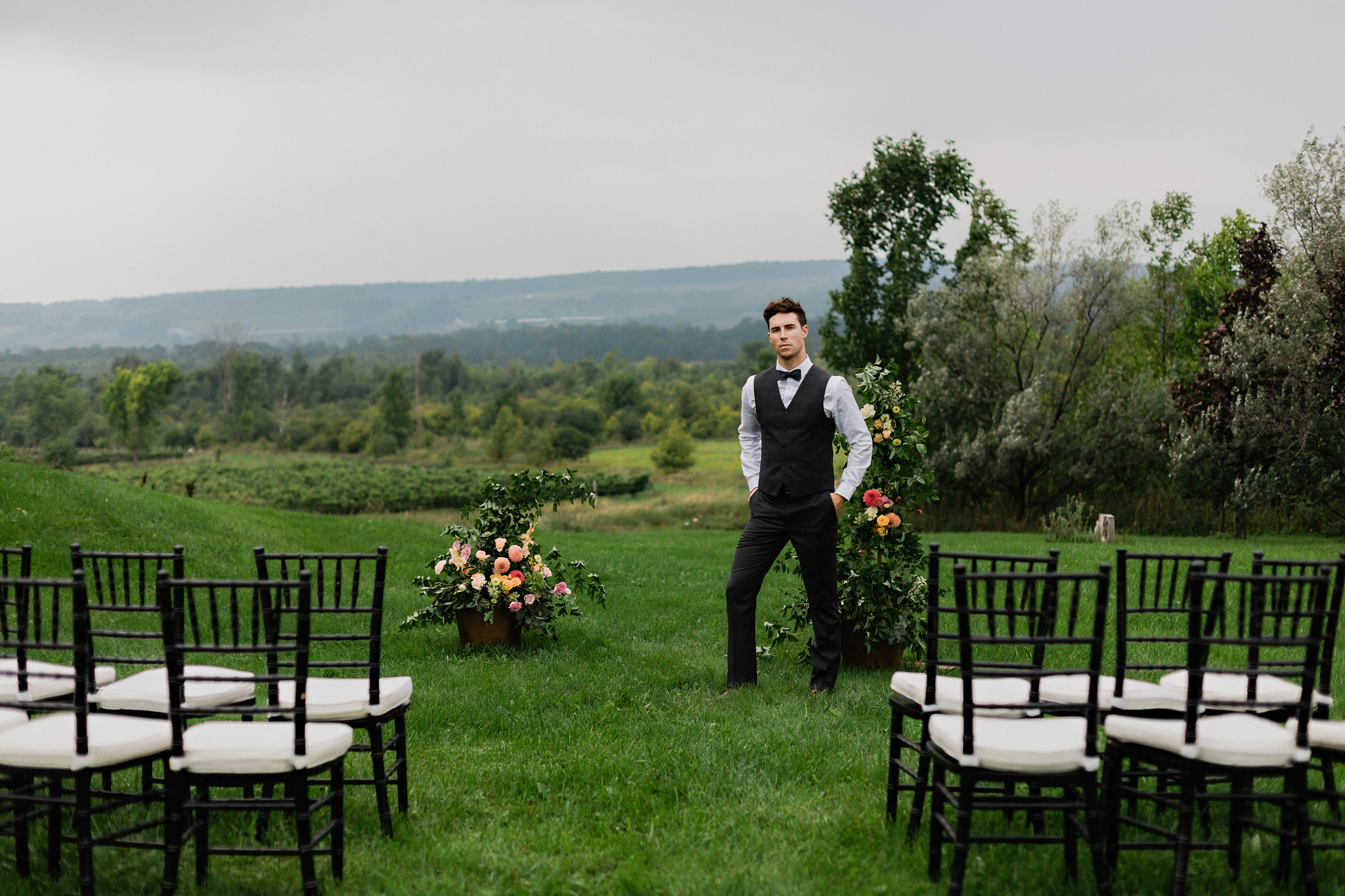 Groom looking dapper in a vest and slacks with sweeping landscap