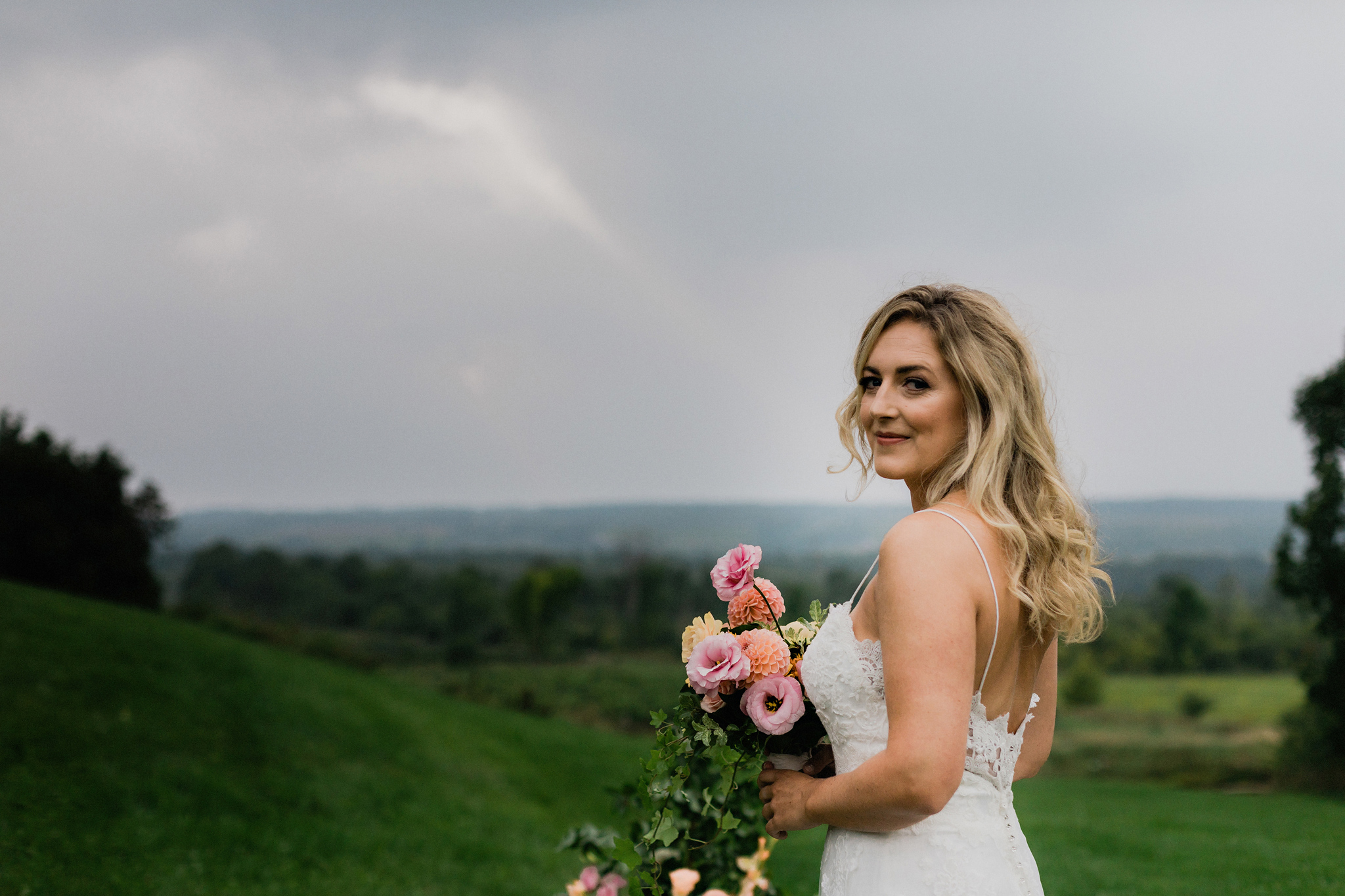 Bride with lace gown, windswept hair and a natural coral bouquet
