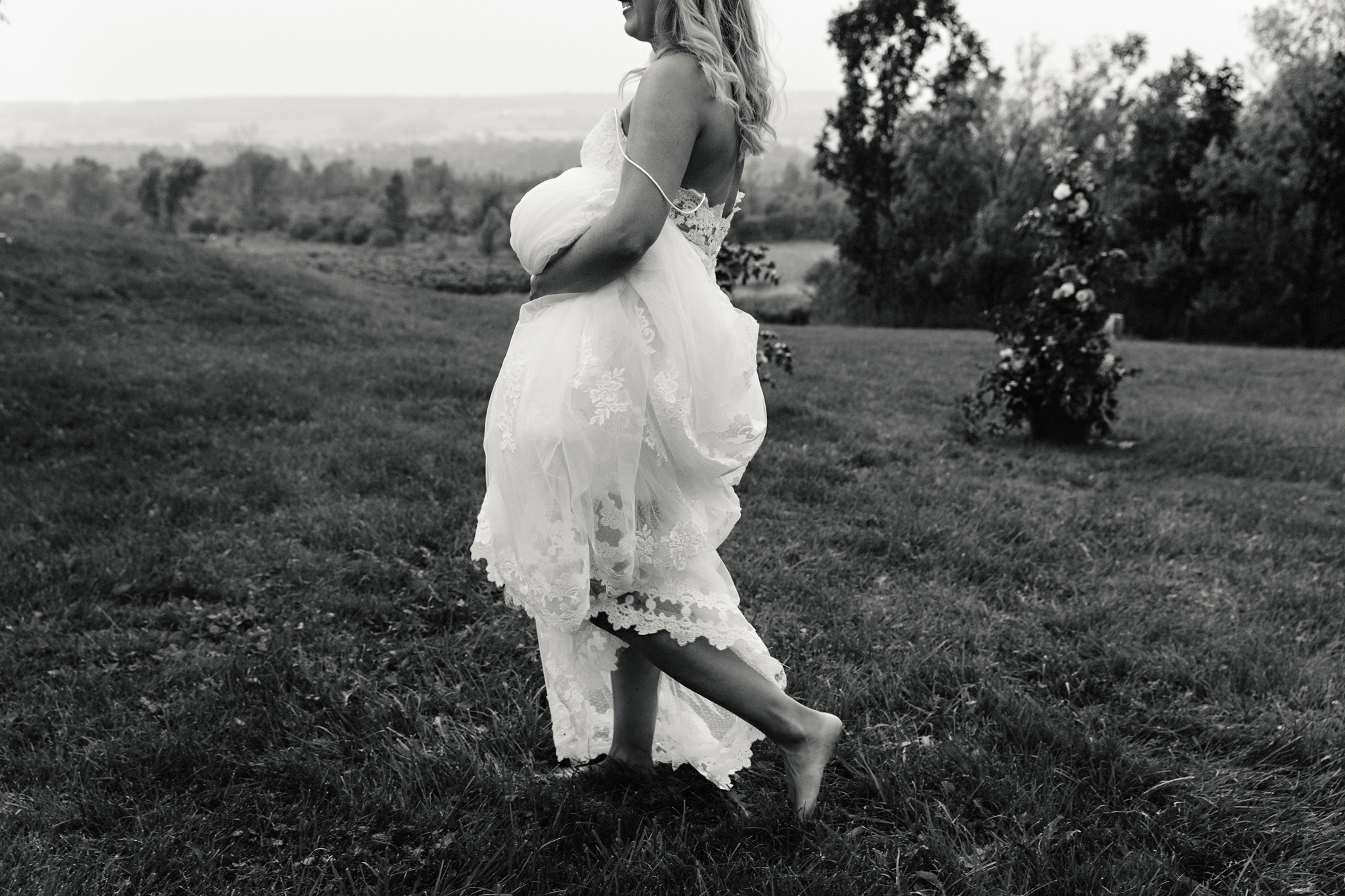 Bride walks barefoot in a field while holding her lace gown at C