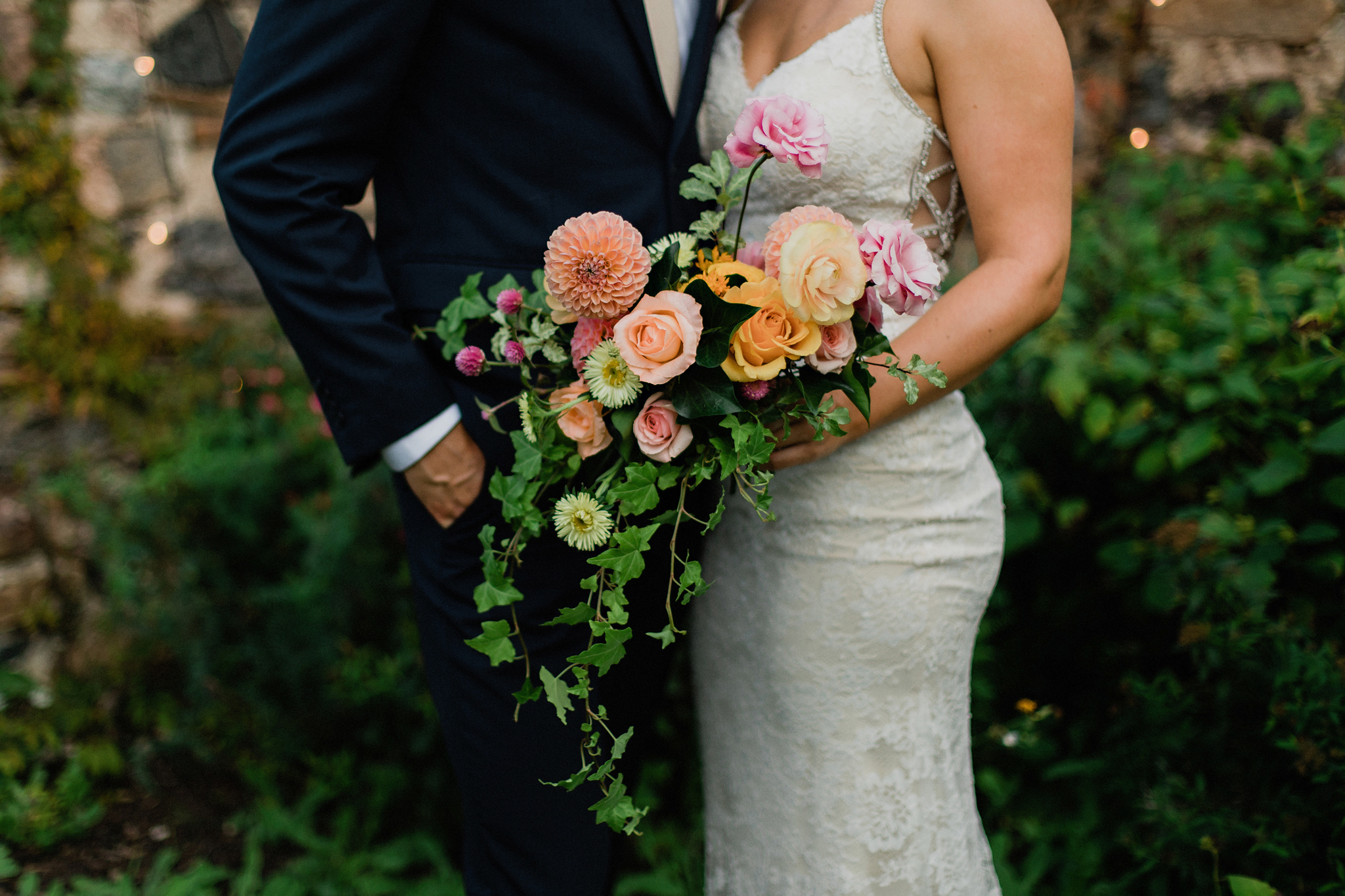A sunset coral toned bridal bouquet with trailing ivy