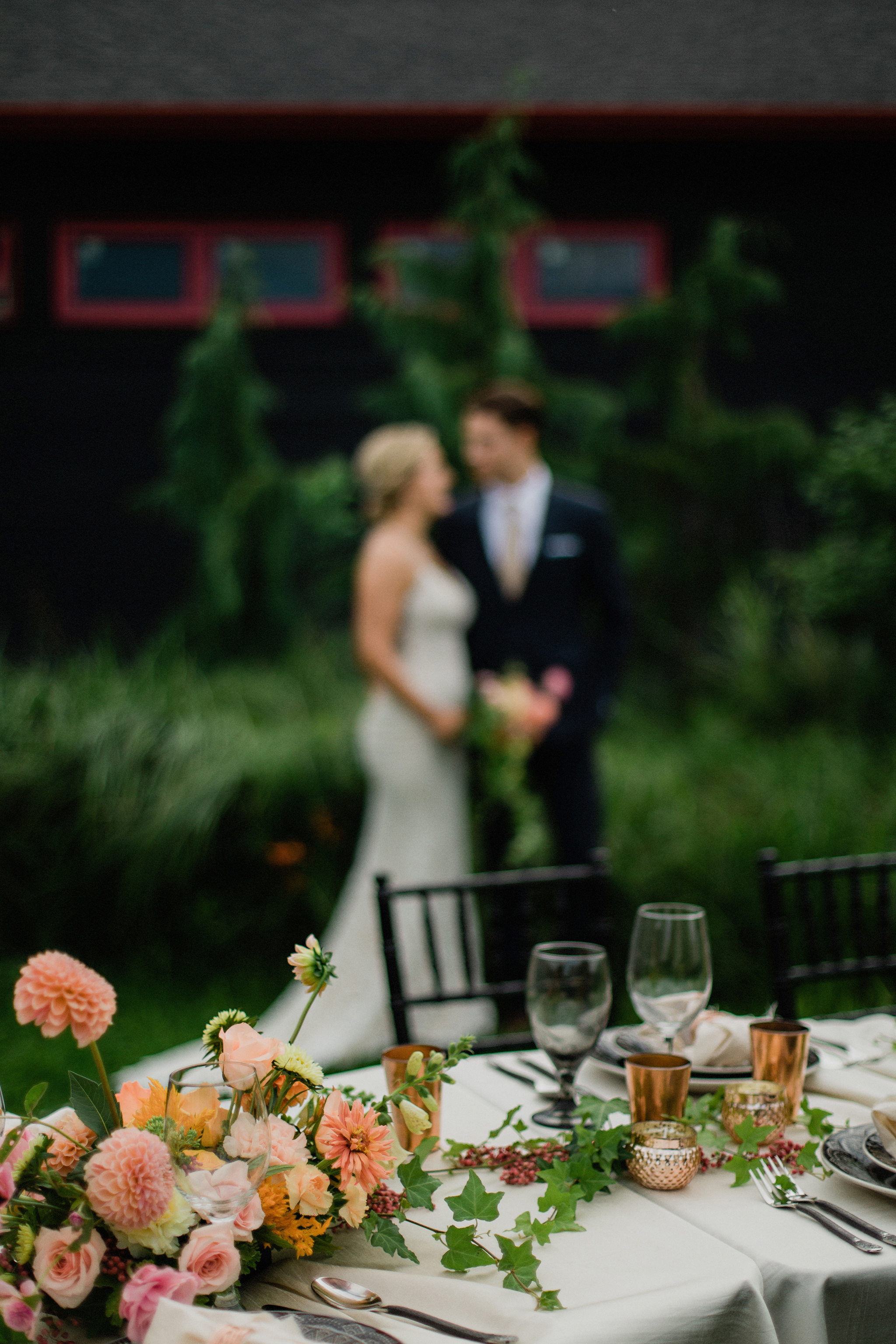 Bride and groom with their coral, copper and smoke table setting