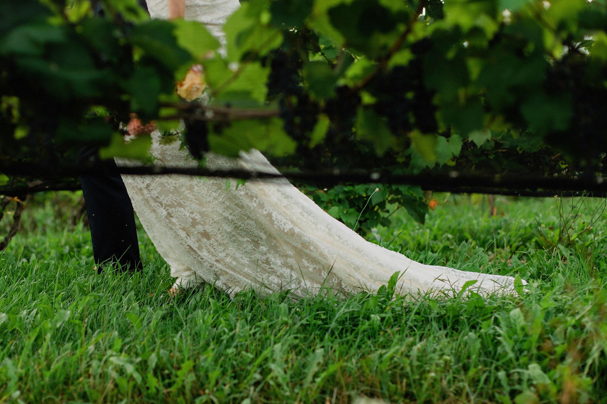 Bride trails lace gown through vineyard at Coffin Ridge Boutique