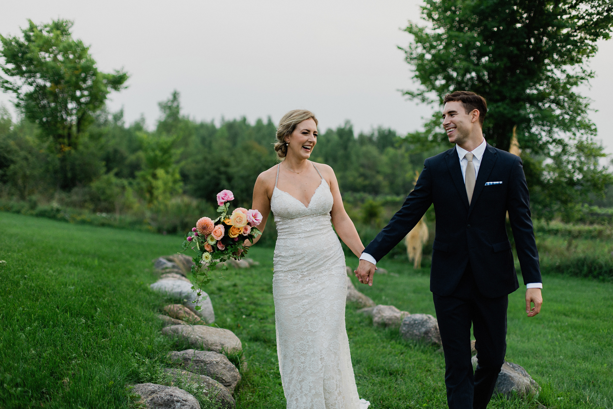 Bride and groom joyfully walk away from ceremony site at Coffin