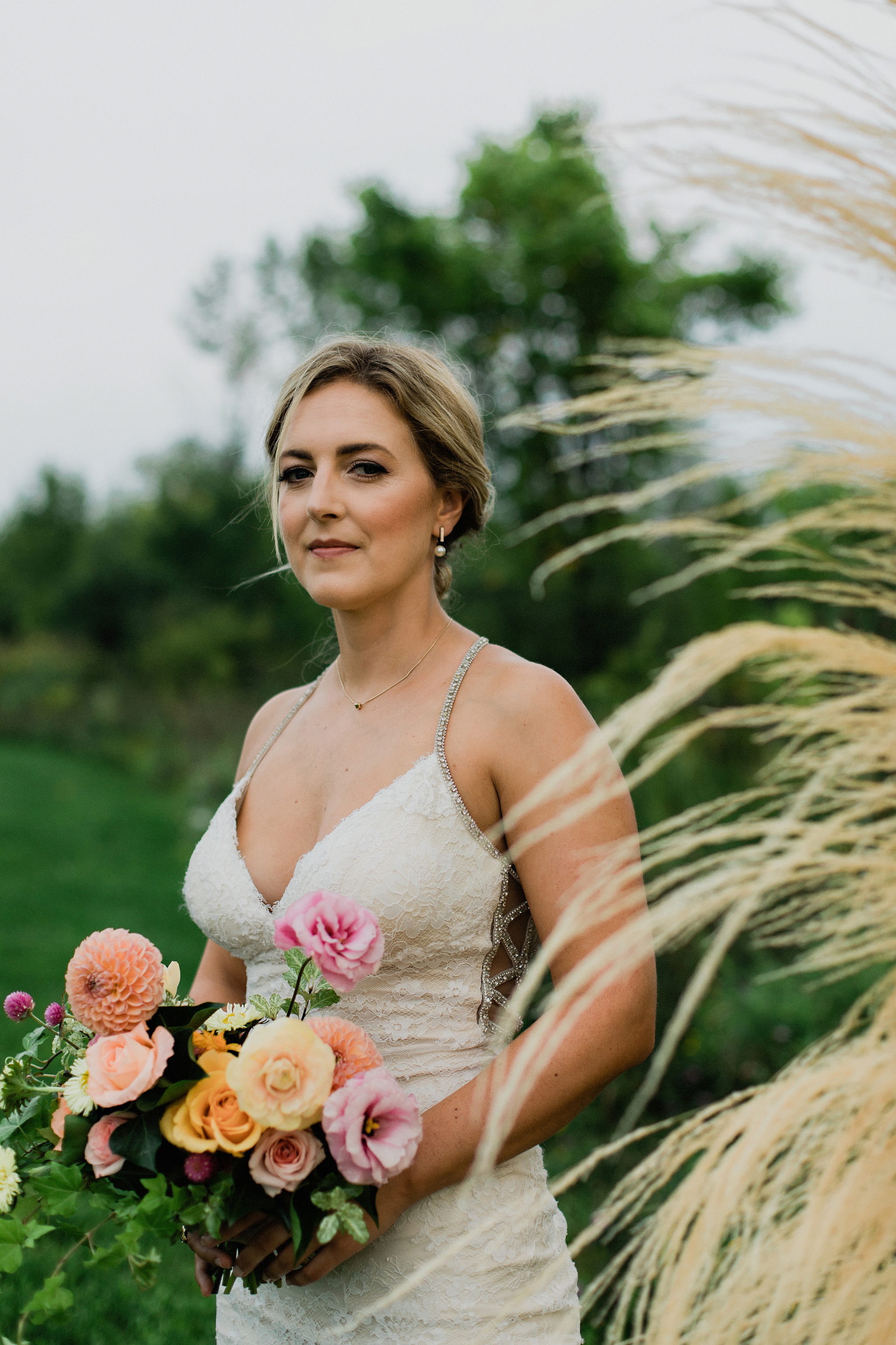 Beautiful bridal portrait with dried grasses and coral toned bou