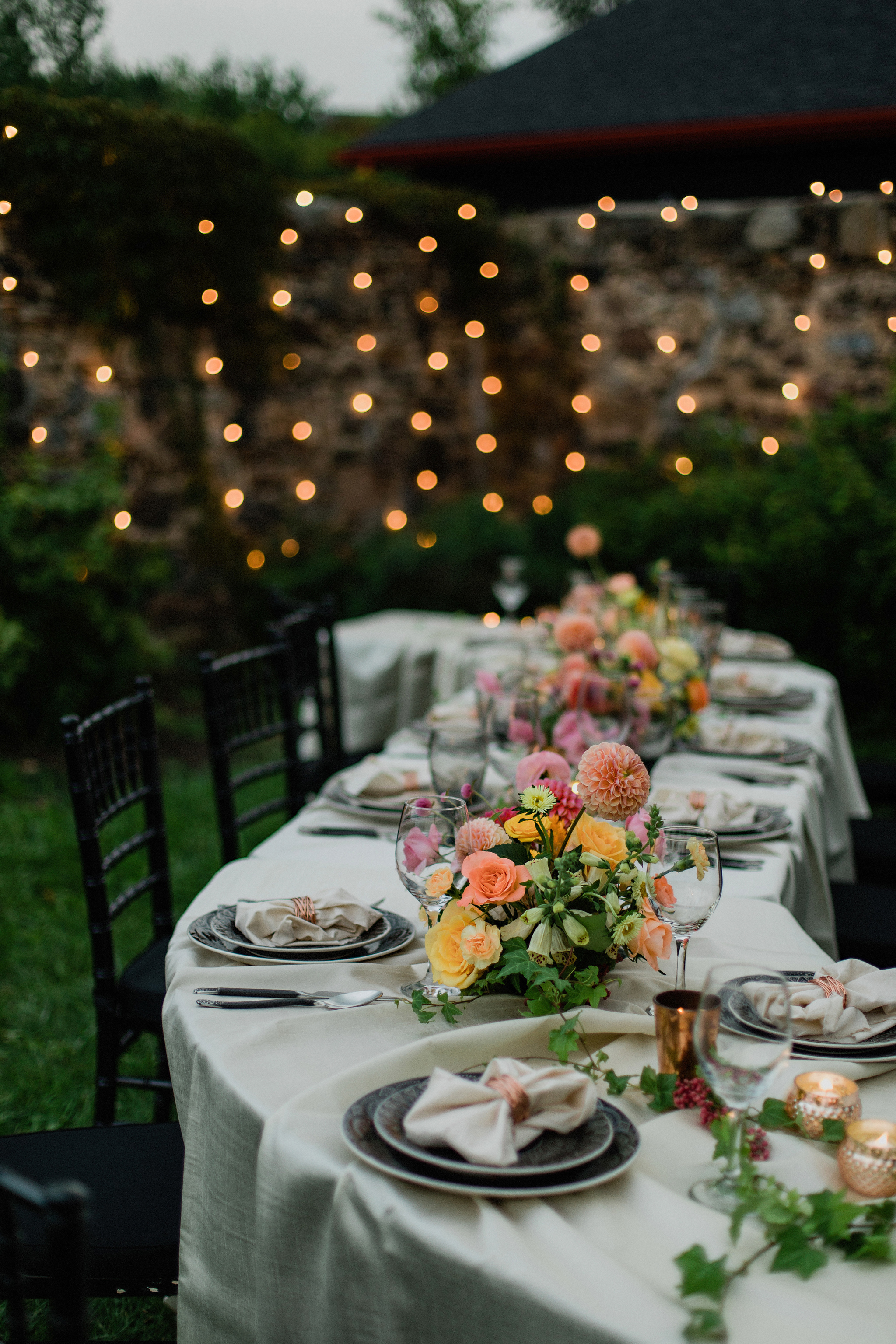 outdoor S curve wedding table with coral toned floral centrepiec