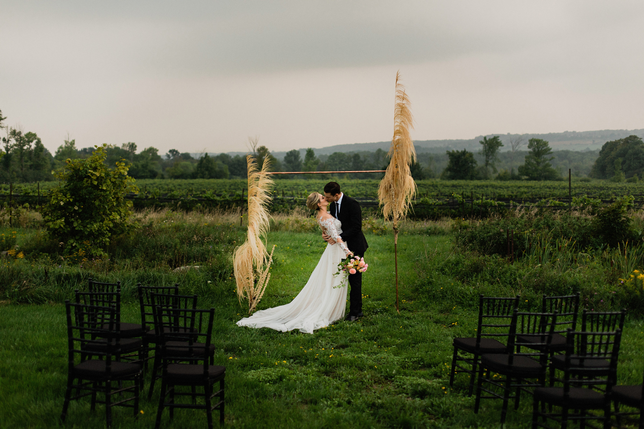 First kiss under copper and dried grasses arch at Coffin Ridge B