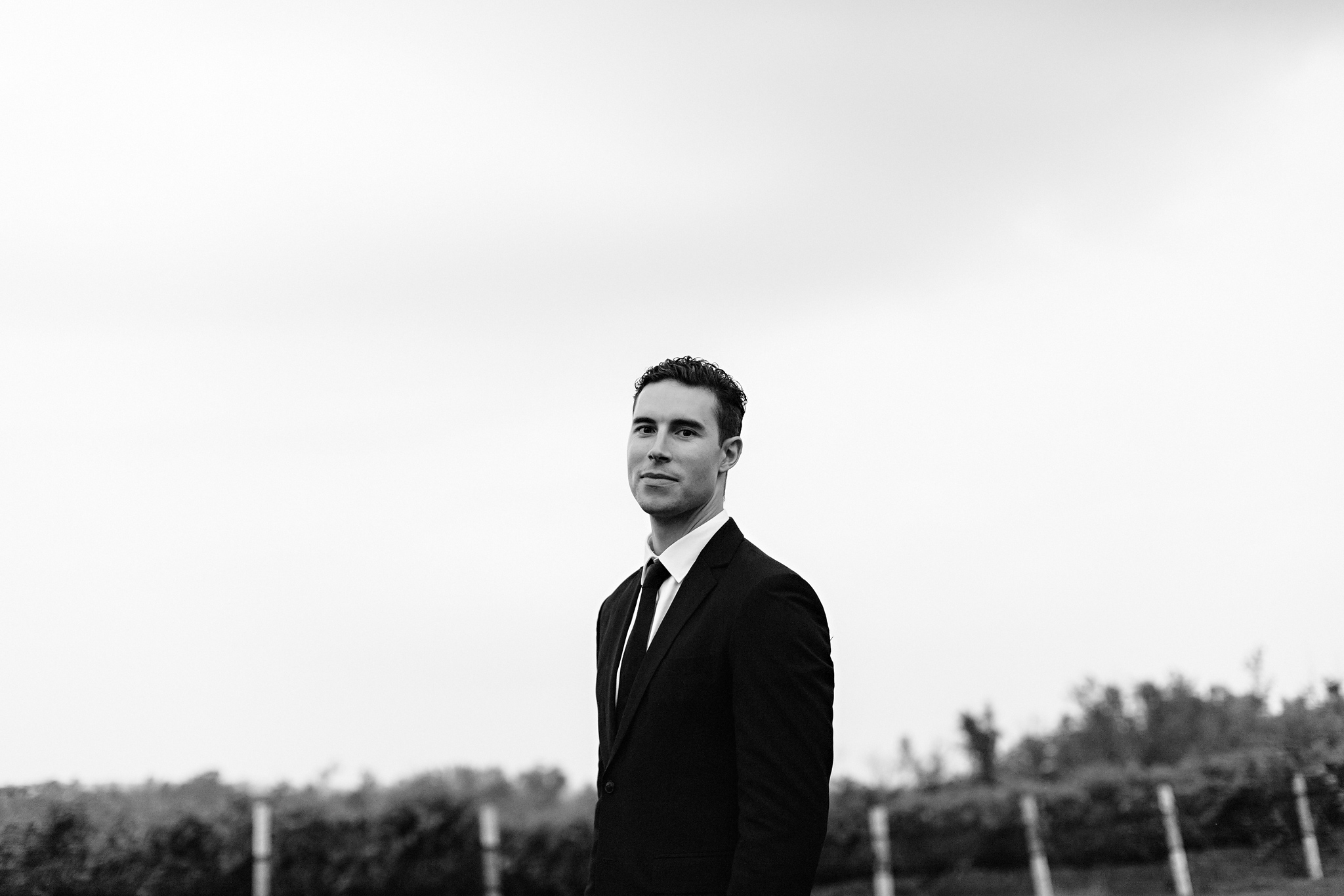 Handsome groom stands in the vineyards in classic black suit at