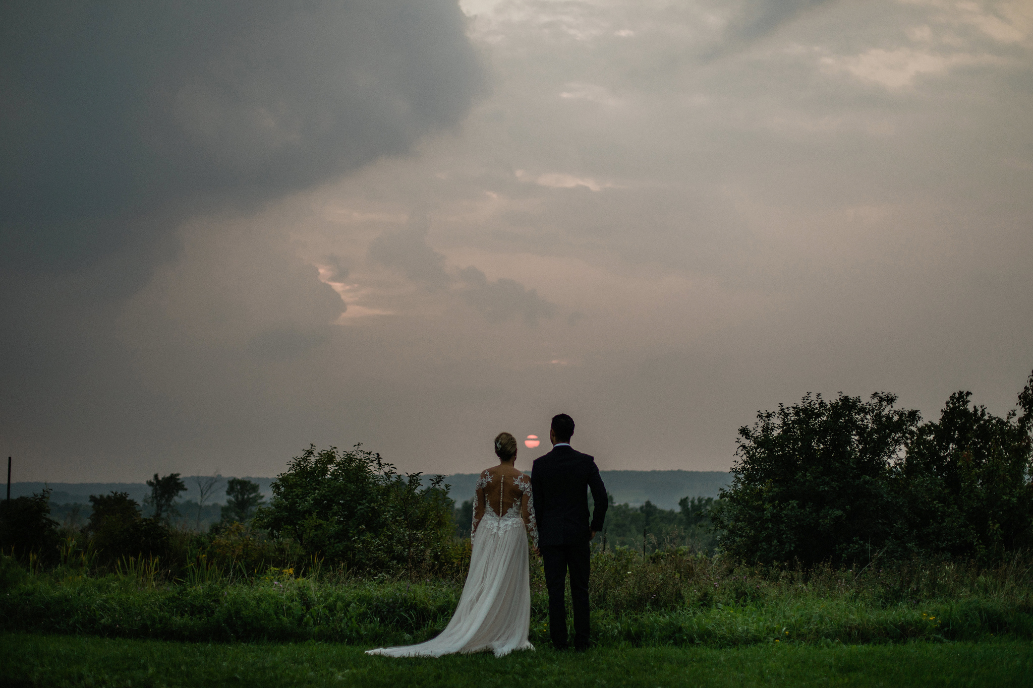 Bride and groom watching the dramatic sunset at Coffin Ridge Bou