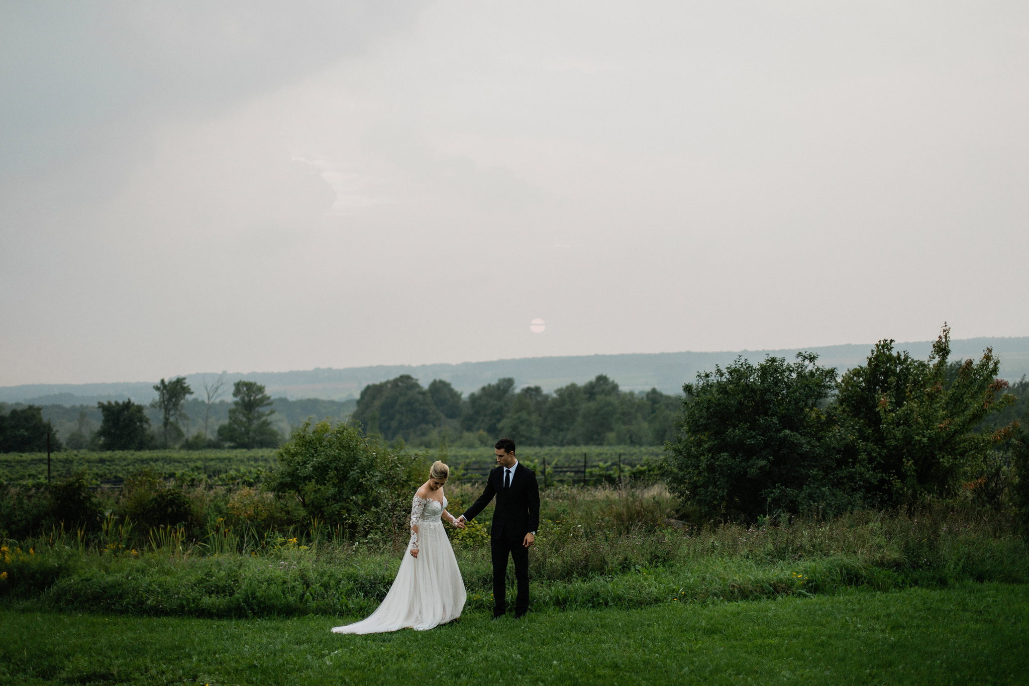 Bride and groom stand in field overlooking vineyards at Coffin R