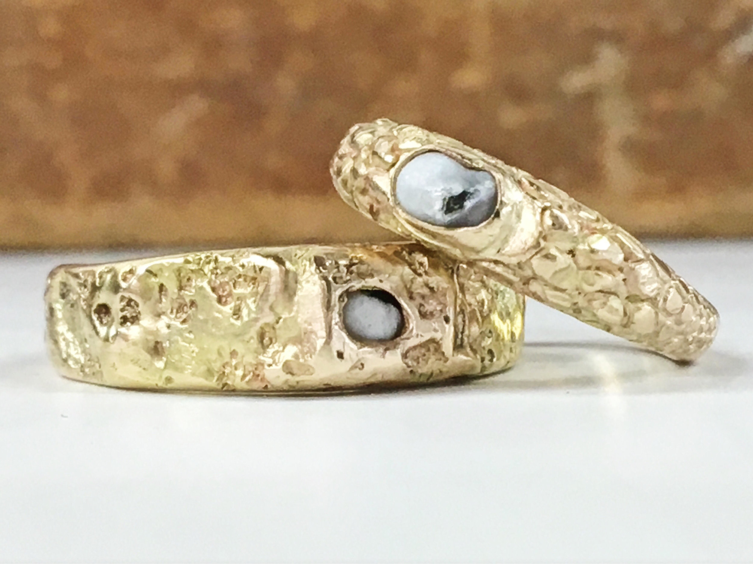 Custom pair of engagement rings carved in the likeness of snake skin and rock textures with bezel setfresh water pearls that my clients found while eating oysters together on the East Coast.