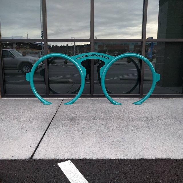Bike parking is up at @islandoptometry from the desk of @makenorthwest . Love the color contrast against the earth tone storefront! #biketowork