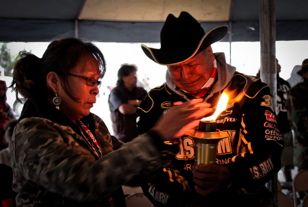 """""""A Navajo Gold Star family receiving the strength and warmth of the ceremonial torch as they remember their lost one during the 9th annual Navajo-Hopi Honor Run's torch ceremony. The ceremonial torch is from """"Carry the Flame Across America,"""" a non-profit organization that is dedicated to the honor and memory of Veterans.""""  Photo:    Donovan Shortey   . See more of his work curated at    Navahophotography.org"""