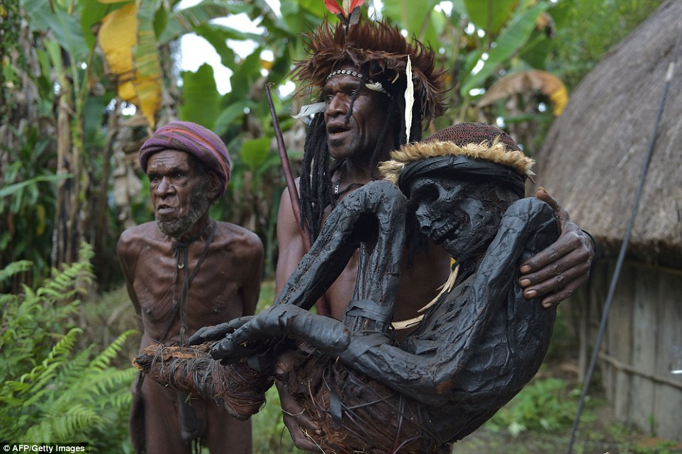 Dani tribe chief carrying smoke-preserved ancestor. The Dani live in a remote area of the Papuan central highlands.  Photo: Getty.