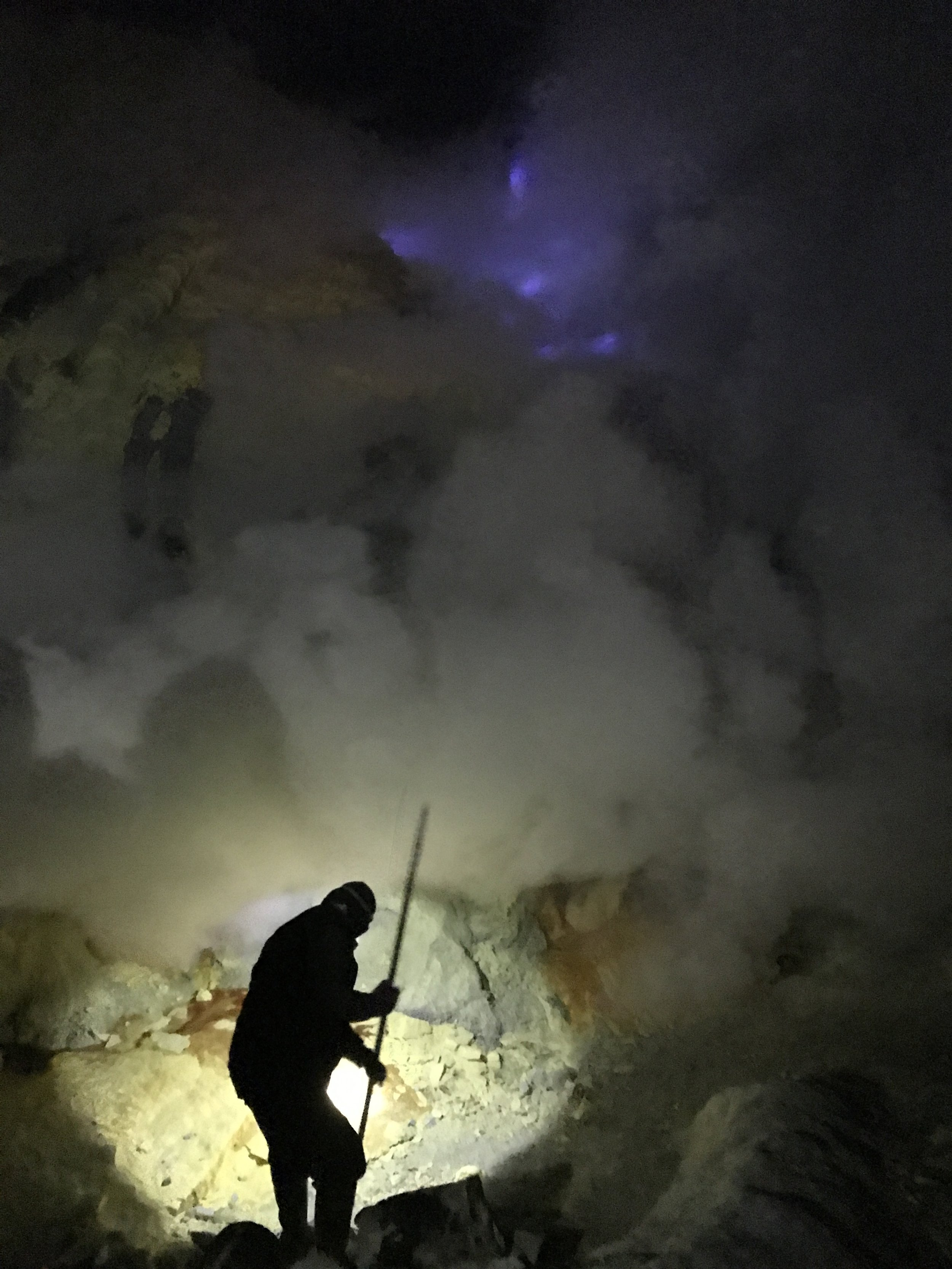A miner chipping at the sulfur