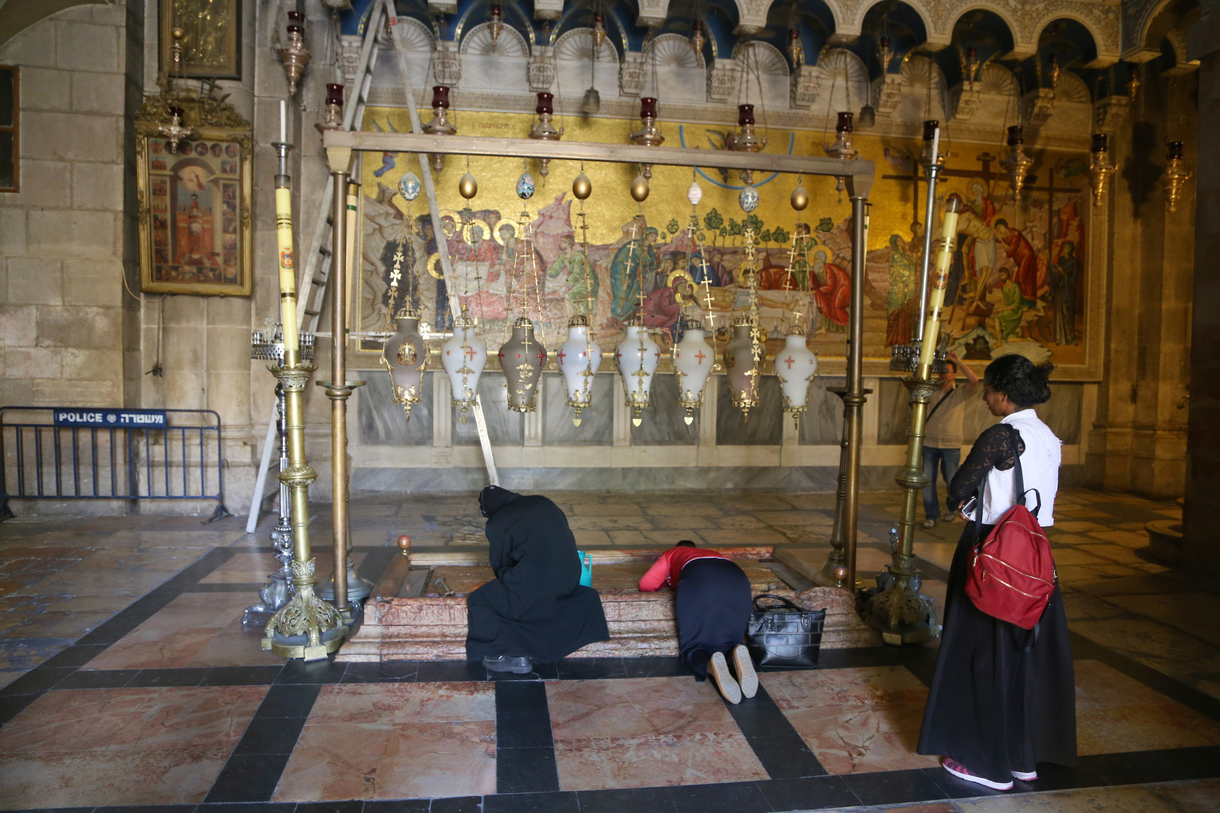 Women at the Stone of Anointing, which tradition believes to be the spot where Jesus' body was prepared for burial.