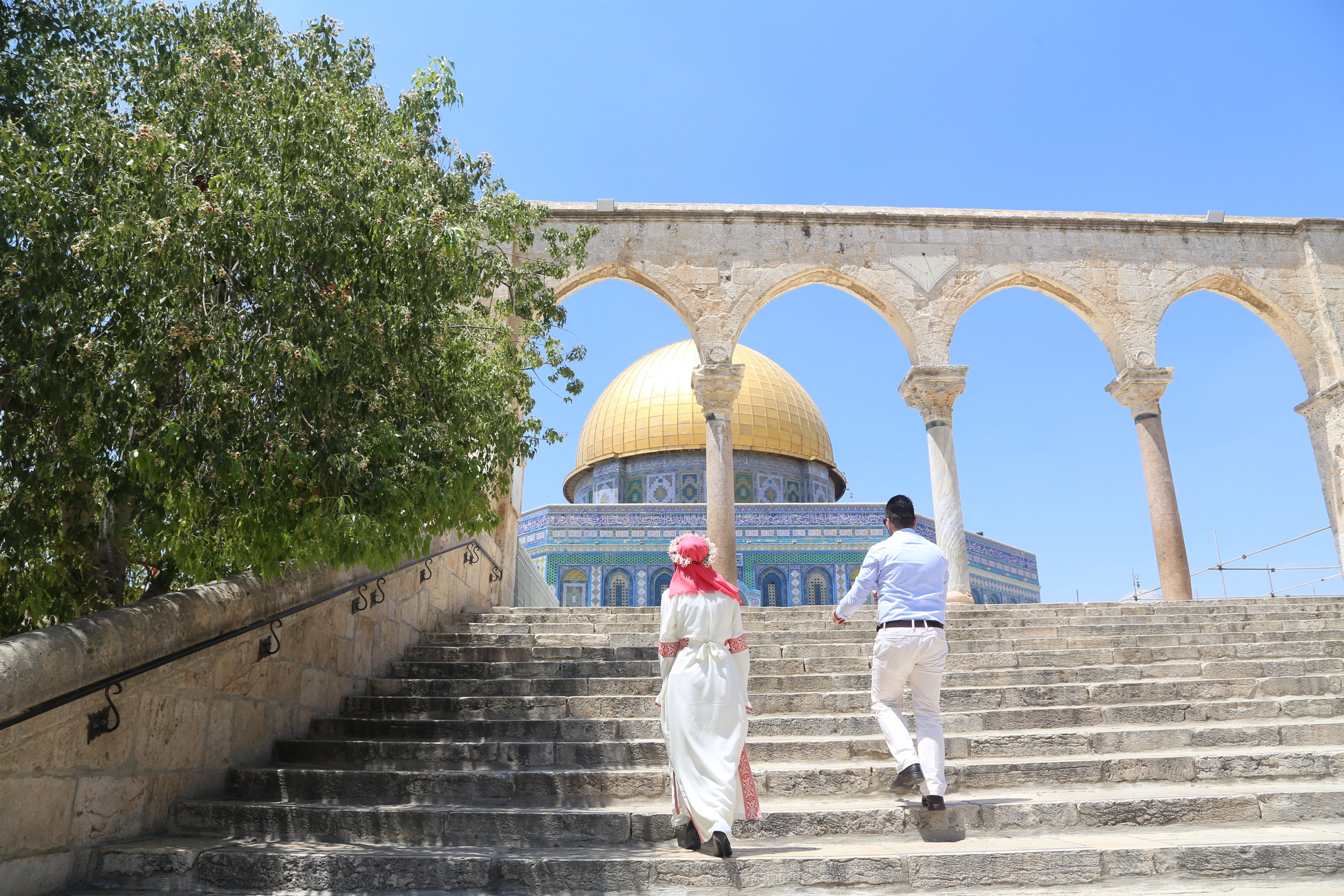 A couple walks towards the Dome of the Rock