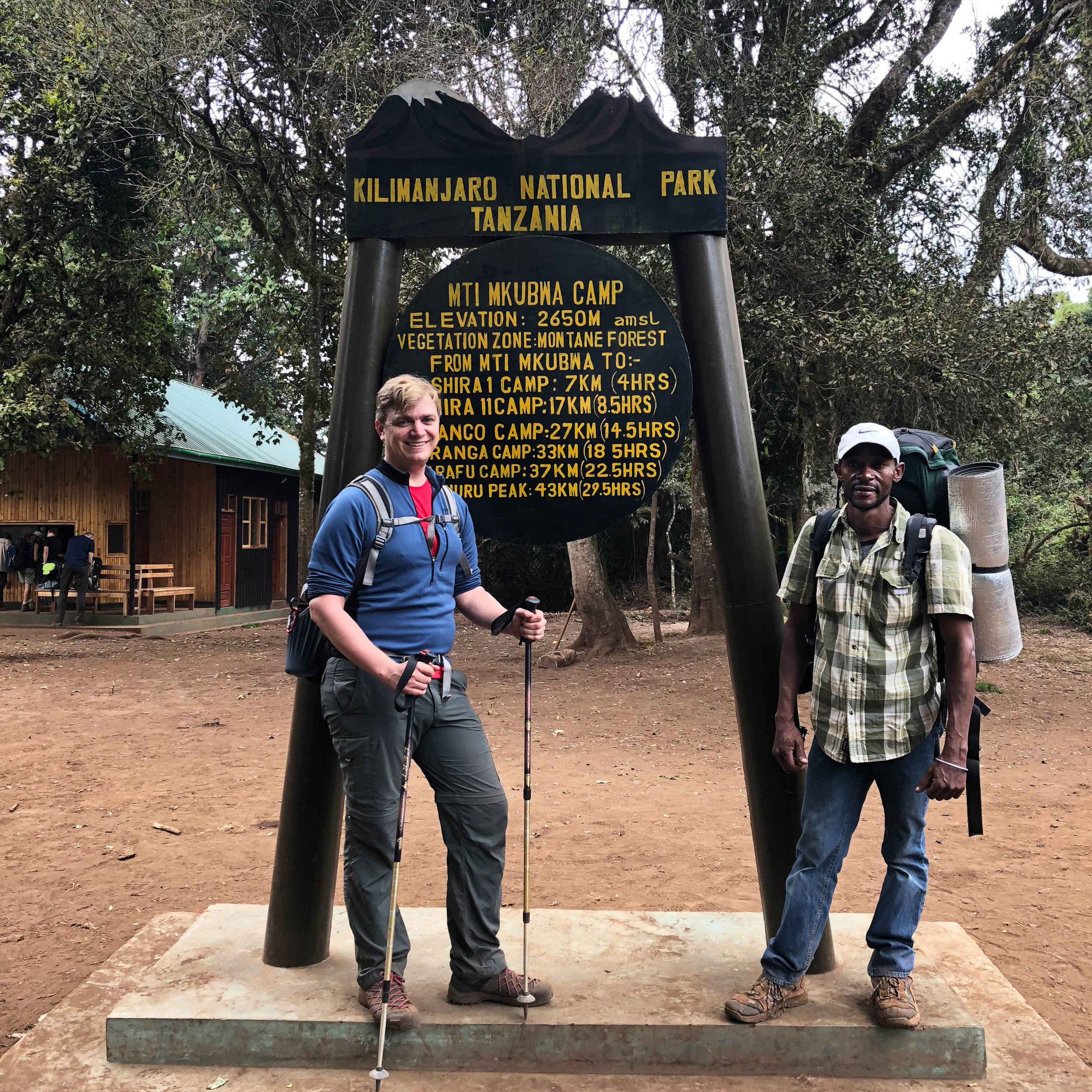 Joel and our assistant guide, Eli, in front of the sign welcoming us into camp.