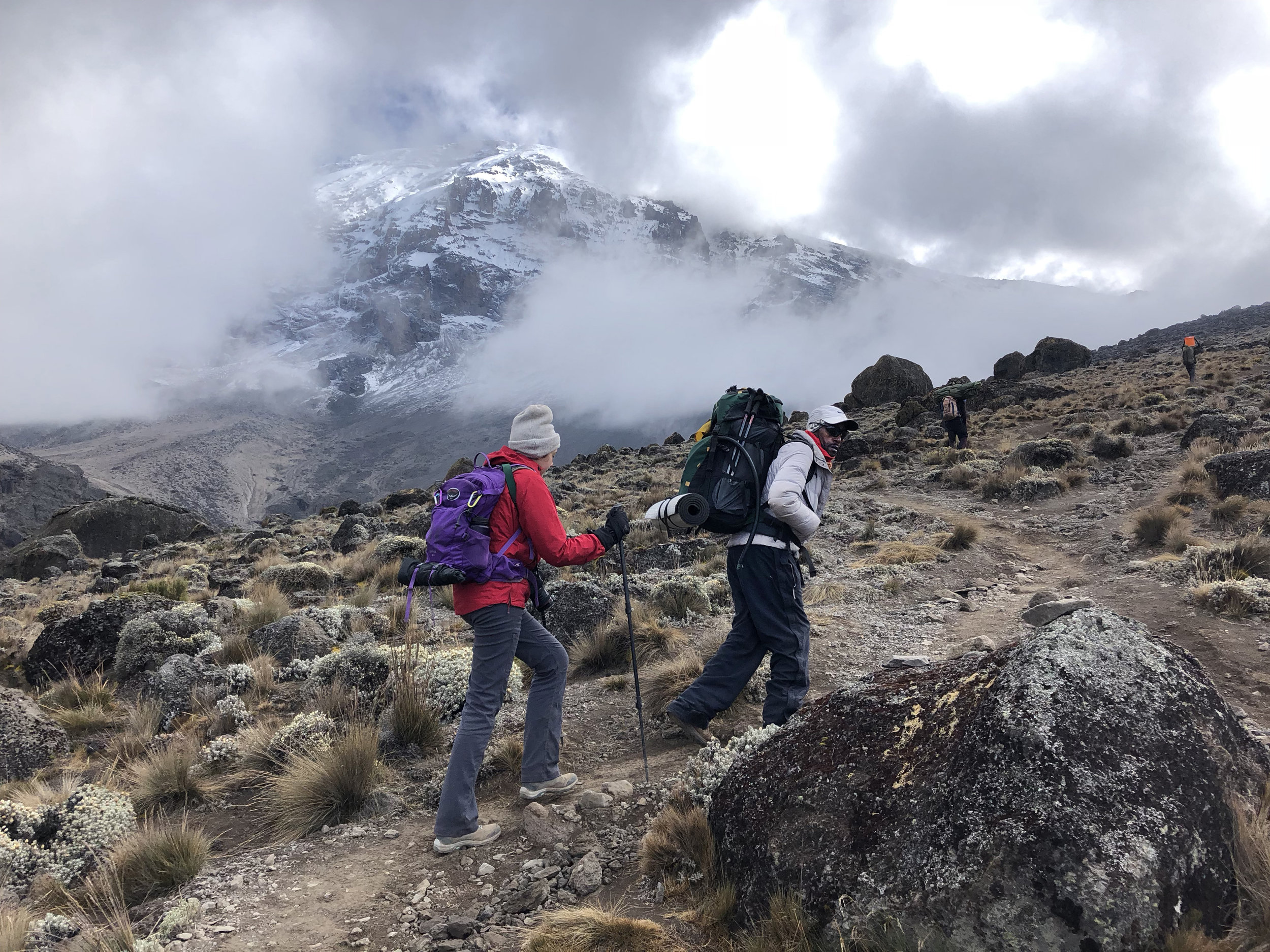 Eli, our assistant guide, and me close behind on the trail with Mt Kilimanjaro looming in the background.
