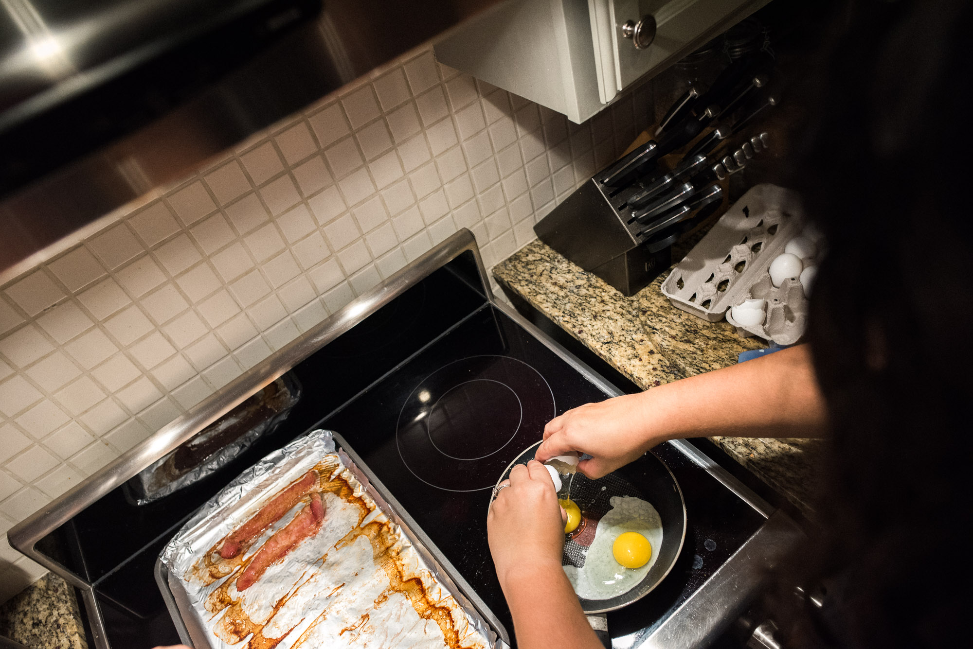 mom cracks eggs over a pan for breakfast