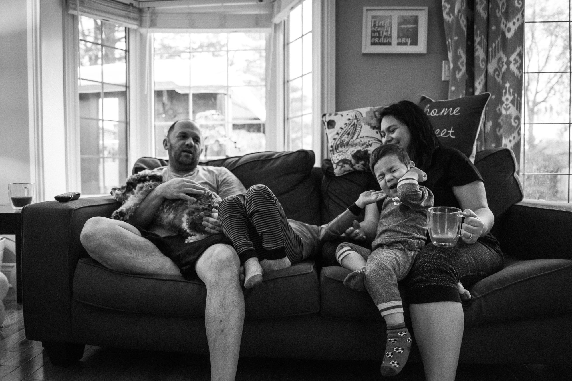 mom and dad enjoy snuggles on the couch with their boys
