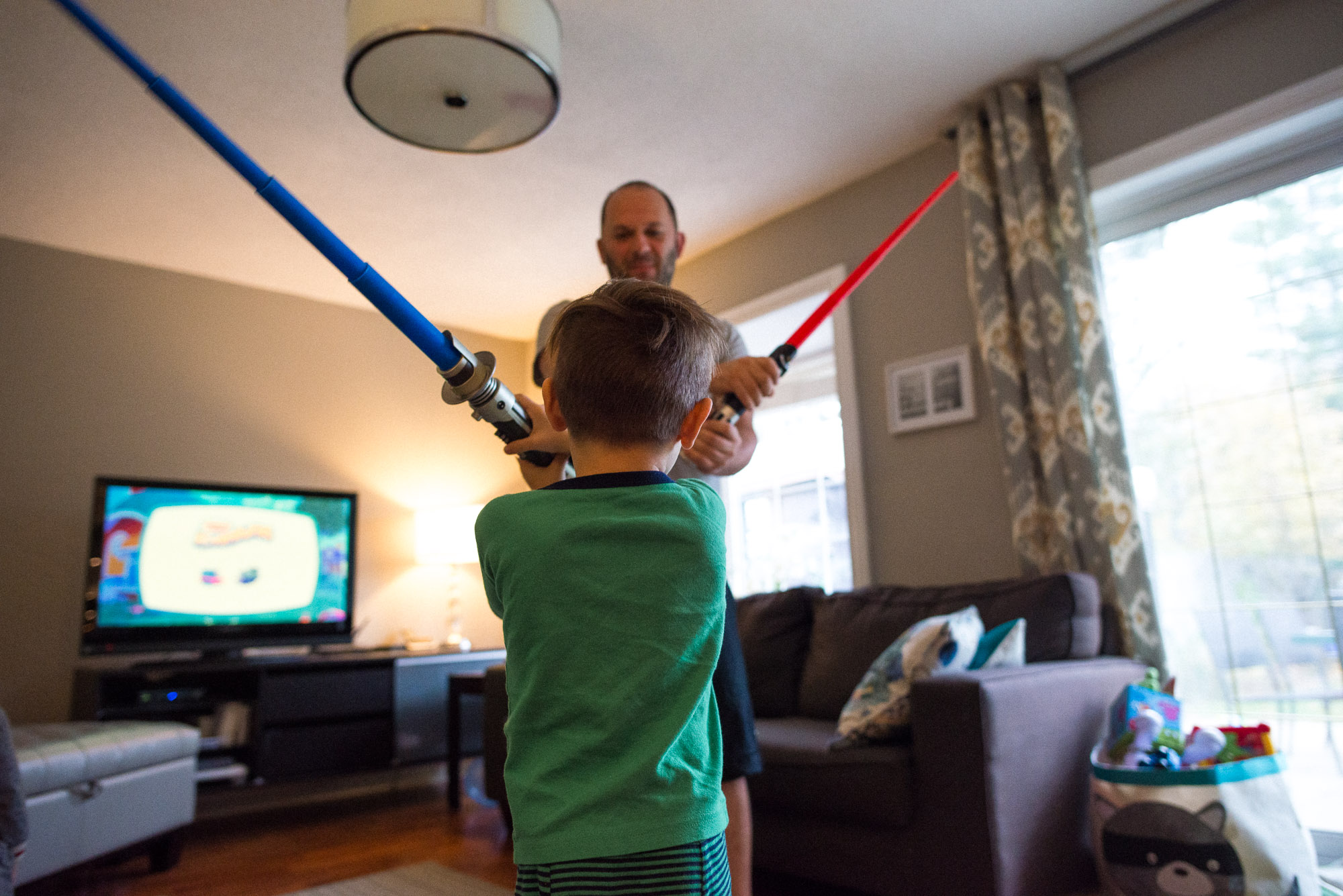 father and son play with light sabers