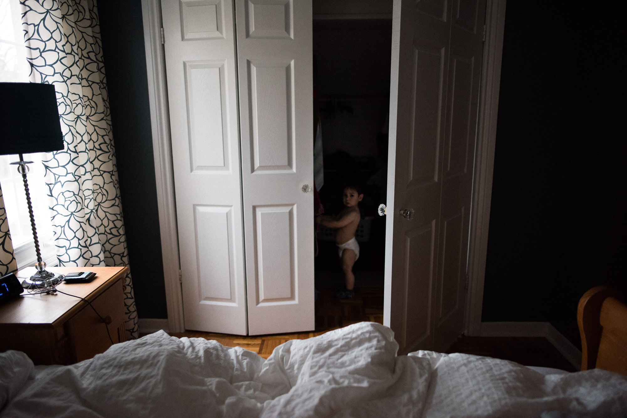 toddler with a diaper hides in a closet