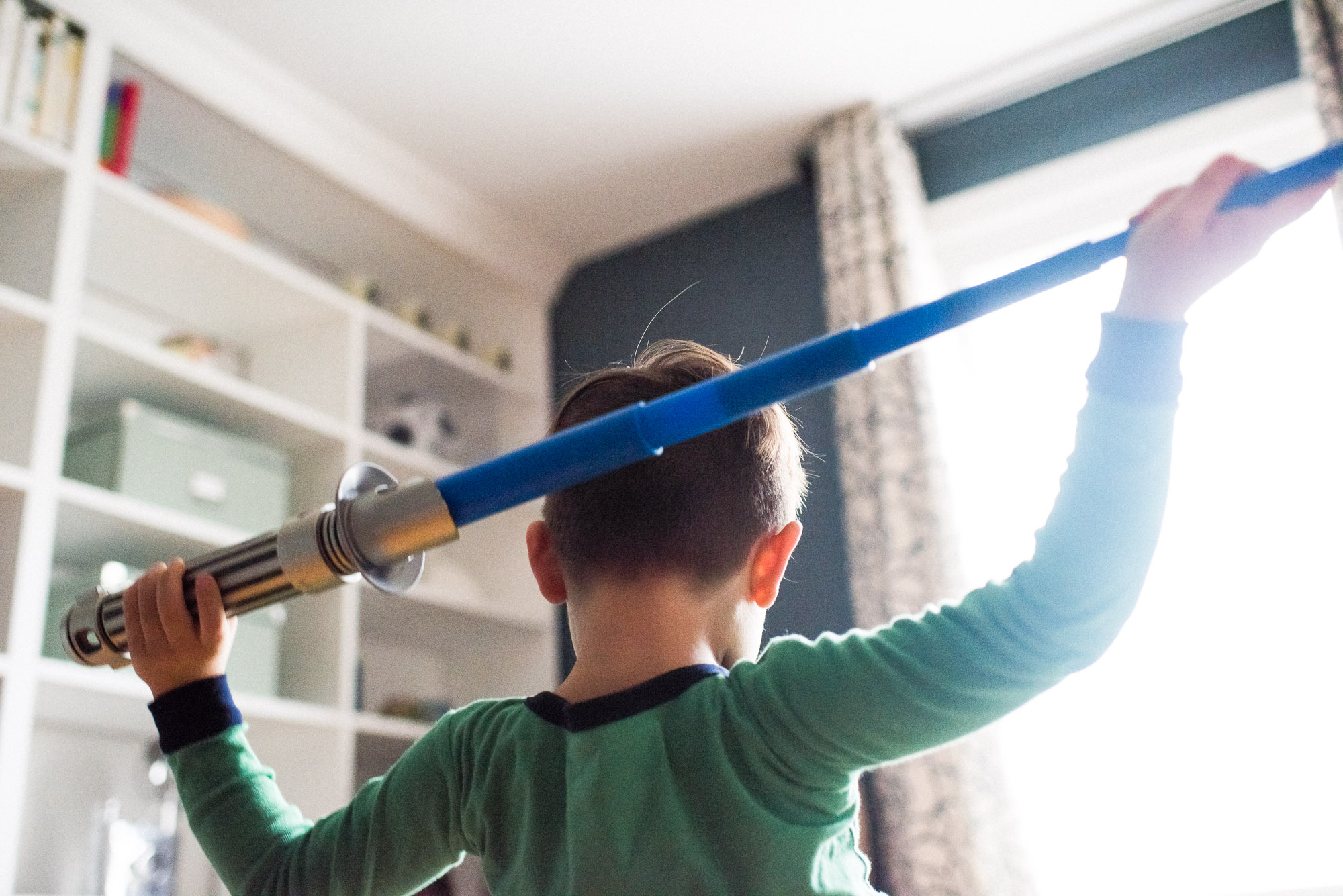 boy holds lightsaber behind his head in front of window