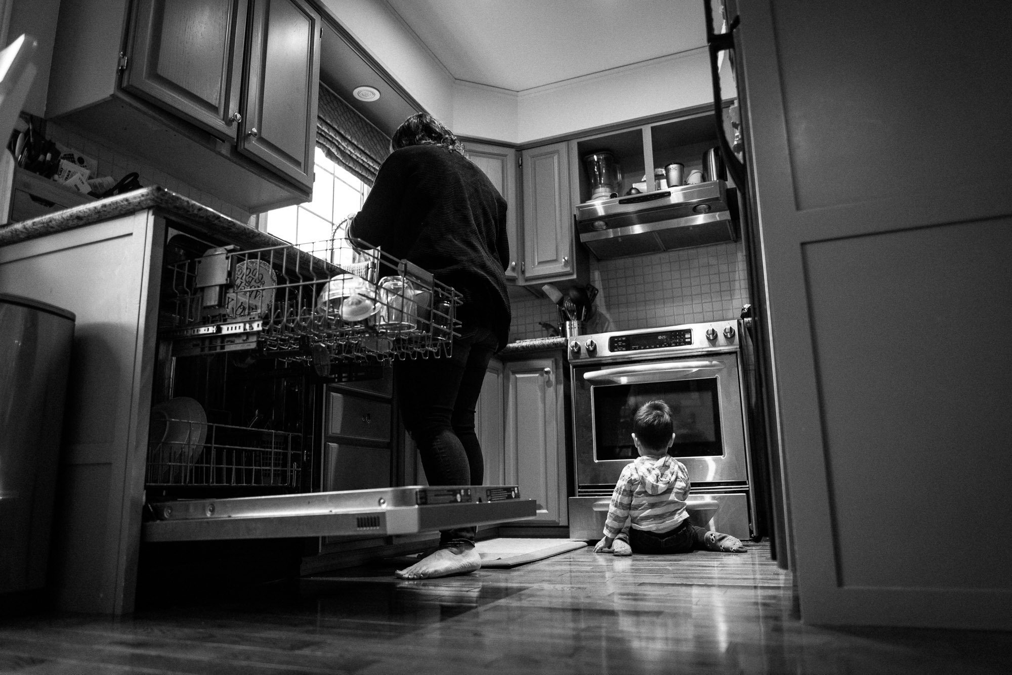 toddler plays on kitchen floor while mom cooks