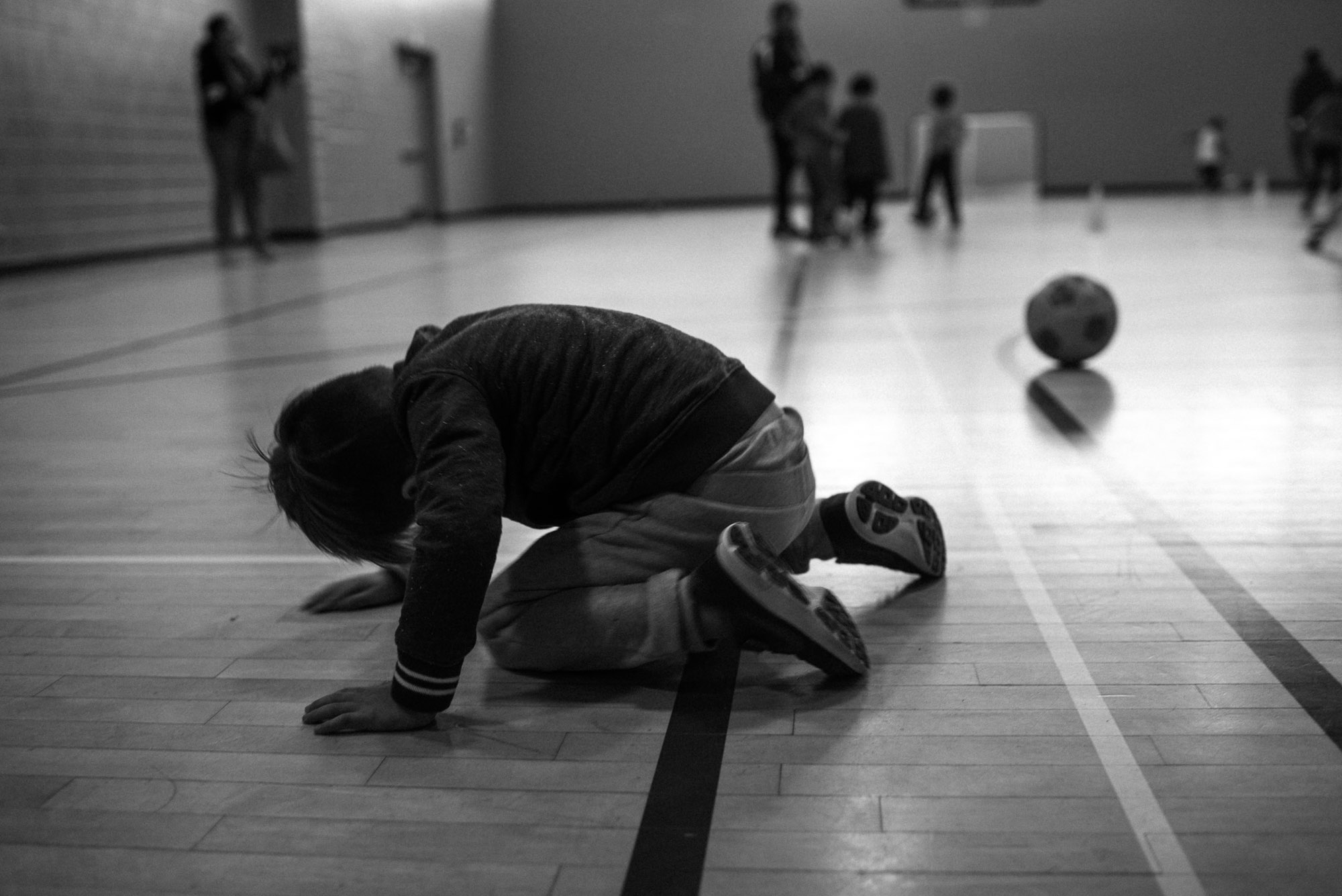 boy reclines on the floor at soccer practice