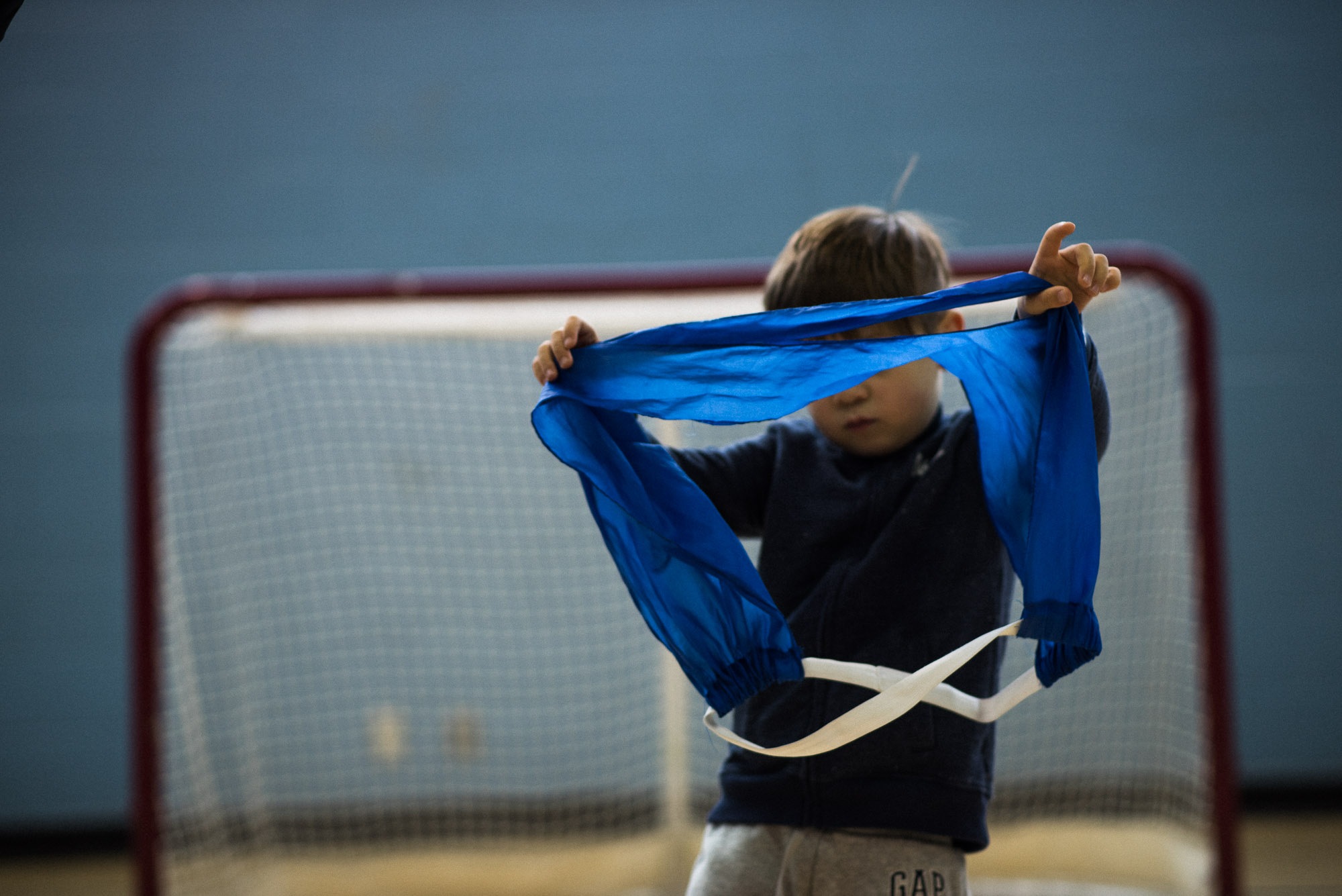 boy holds up blue soccer bib in front of his face