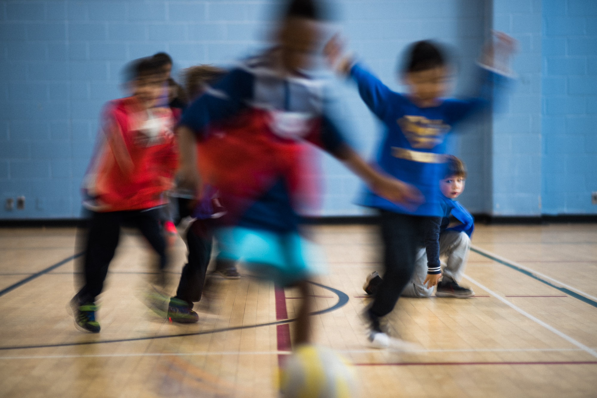 blur of children playing soccer with blue tones