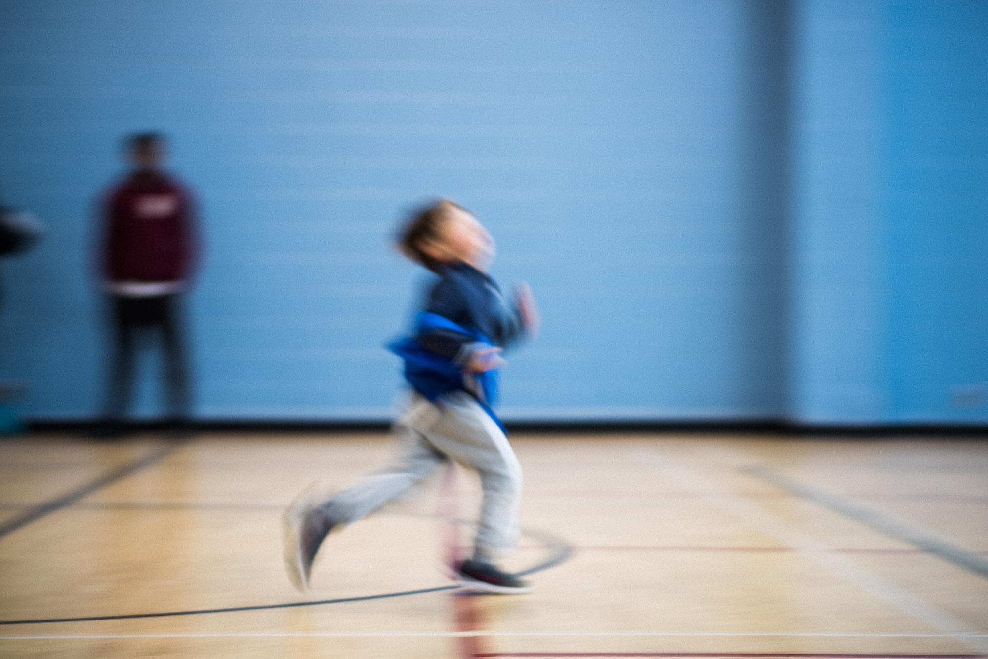 motion blur boy runs at soccer practice dressed in blue bib