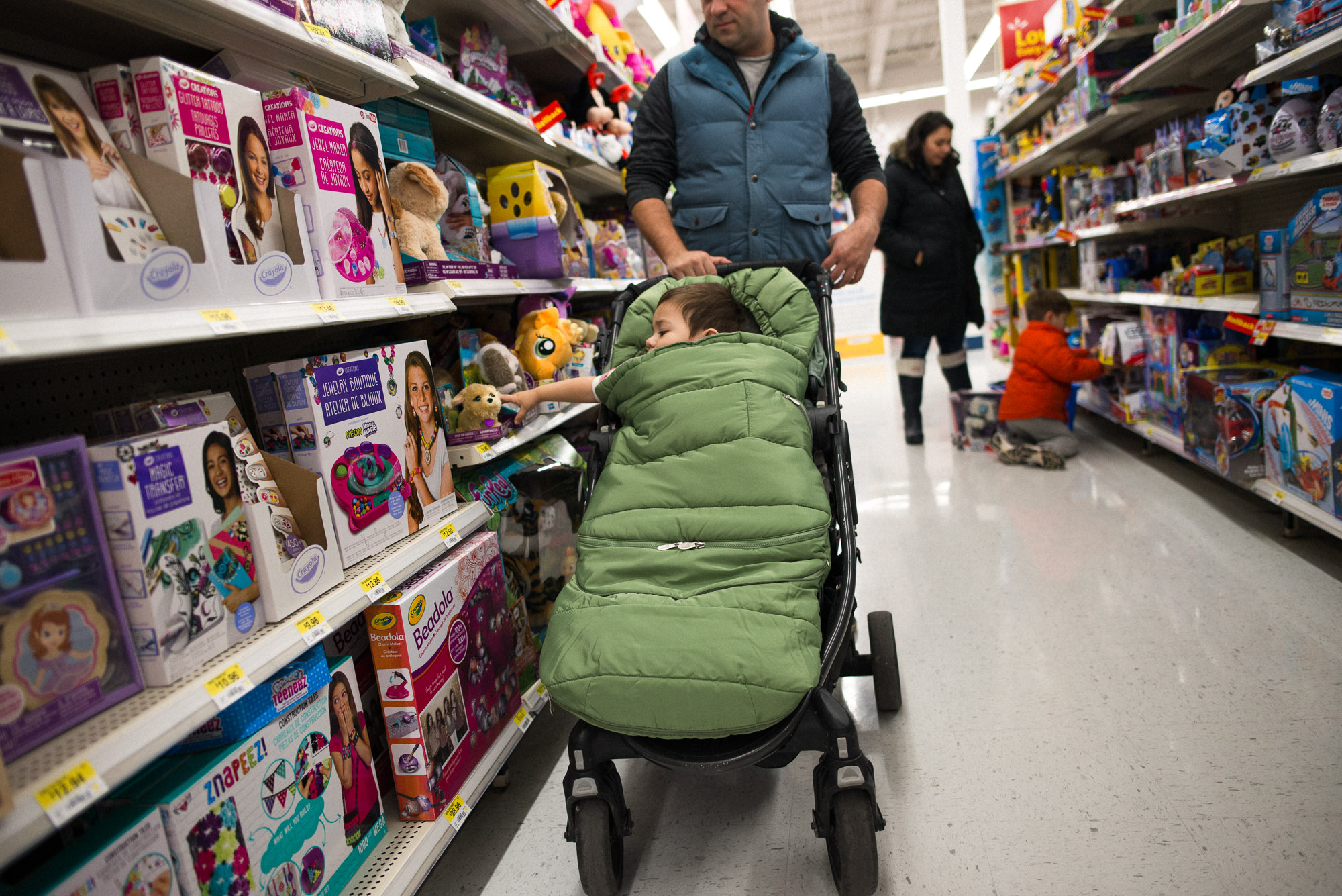 dad pushes stroller as toddler hand shoots out to grab toy off the shelf